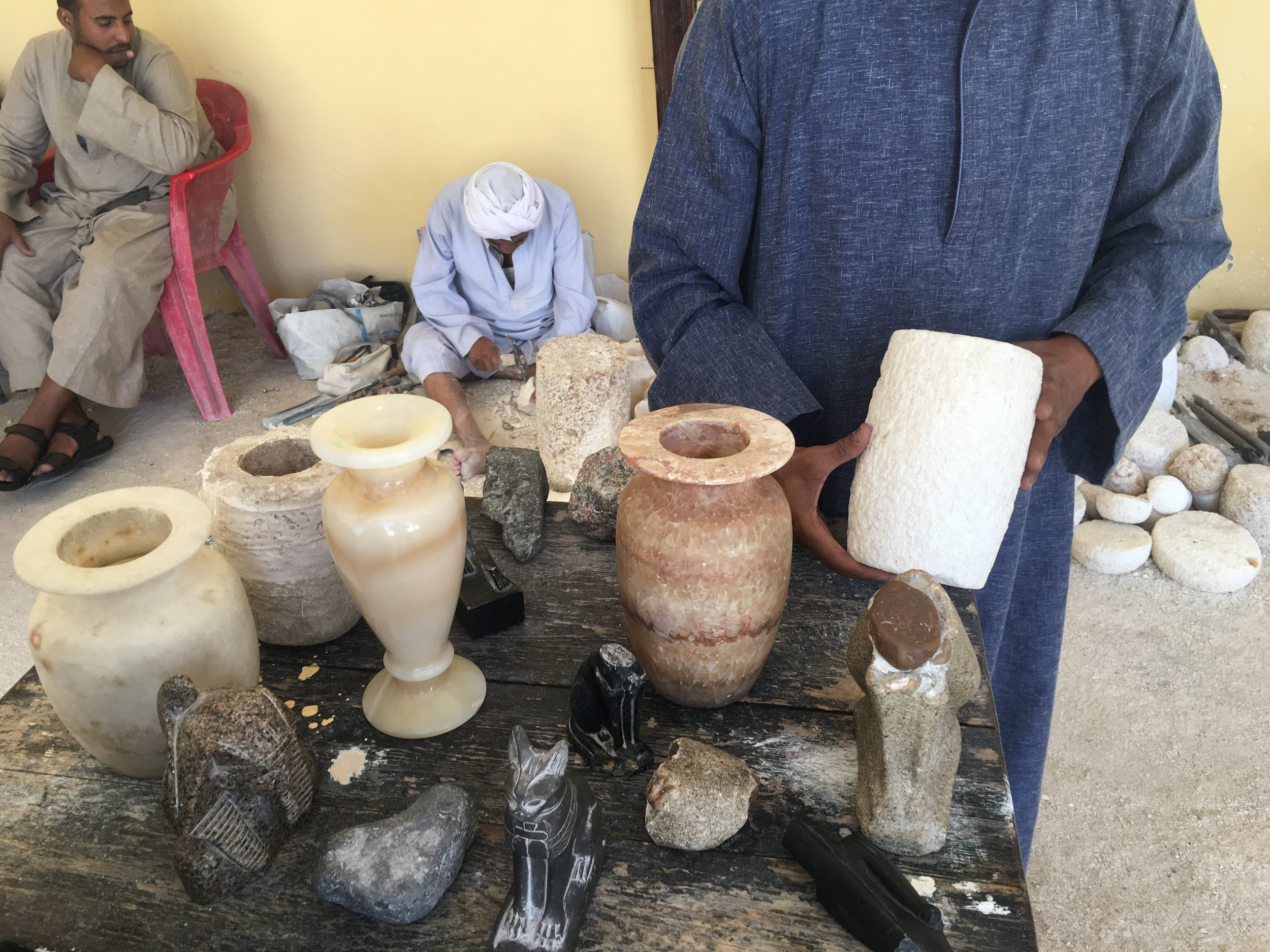 The small statues in the front are carved from basalt but the vases are alabaster and all but the narrow shiny one have been carved by hand. The alabaster carving business has been passed down through generations for centuries in Egypt.