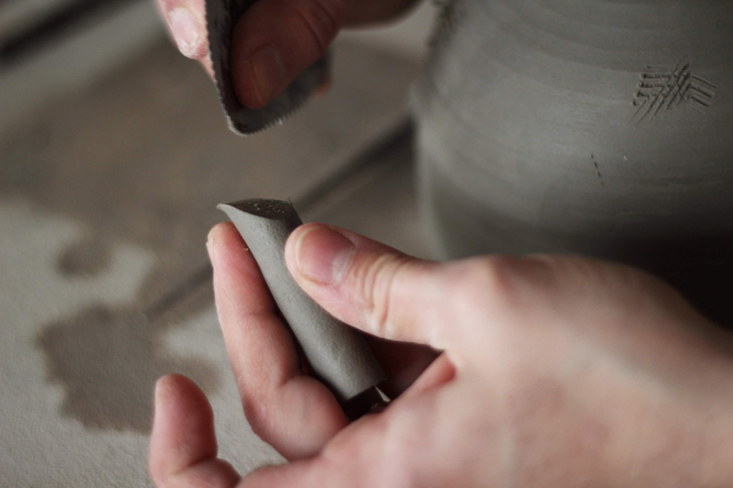 Alicia applies the mug handles and planter legs, smoothing them out to prepare them for dipping in colour. This photo shows a planter getting its legs put on.
