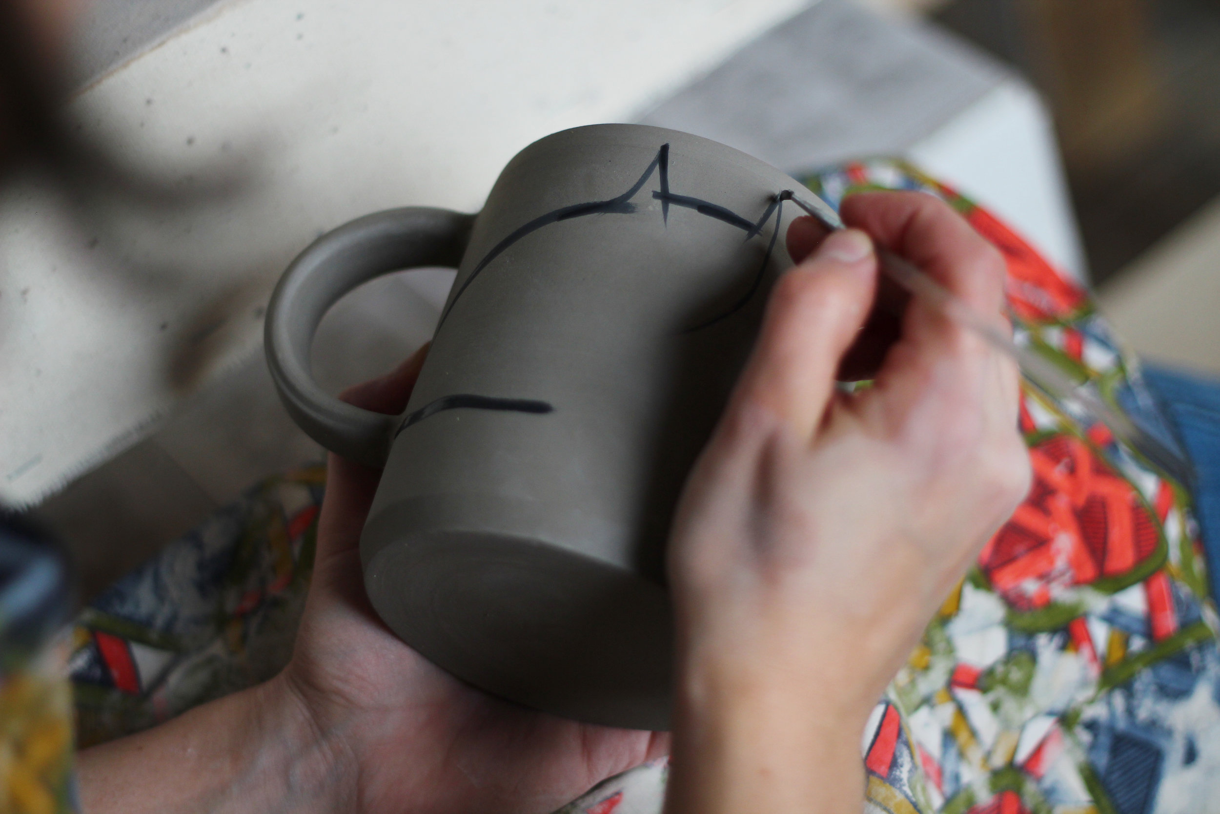 Some pieces, like our cat mug with the tail on the handle, are completely painted by hand, so each one is completely unique and has its own personality! Other pieces have hand-painted details in addition to the engobe dip. These details, like faces and outlines, are hand-painted on with a tiny paintbrush.