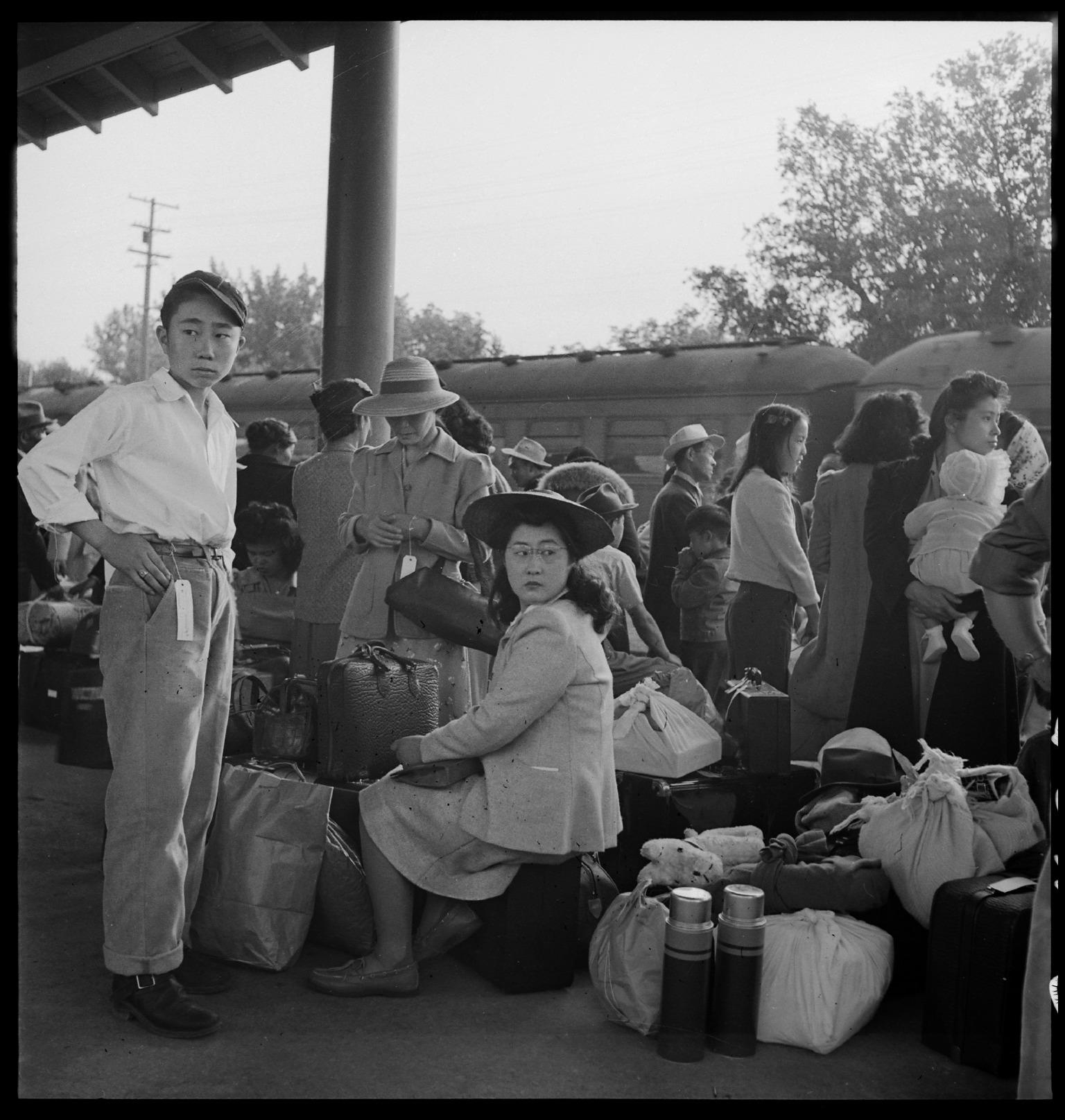 Woodland_CA_Families_of_Japanese_ancestry_with_their_baggage_at_railroad_station_awaiting_NARA_537804.jpg