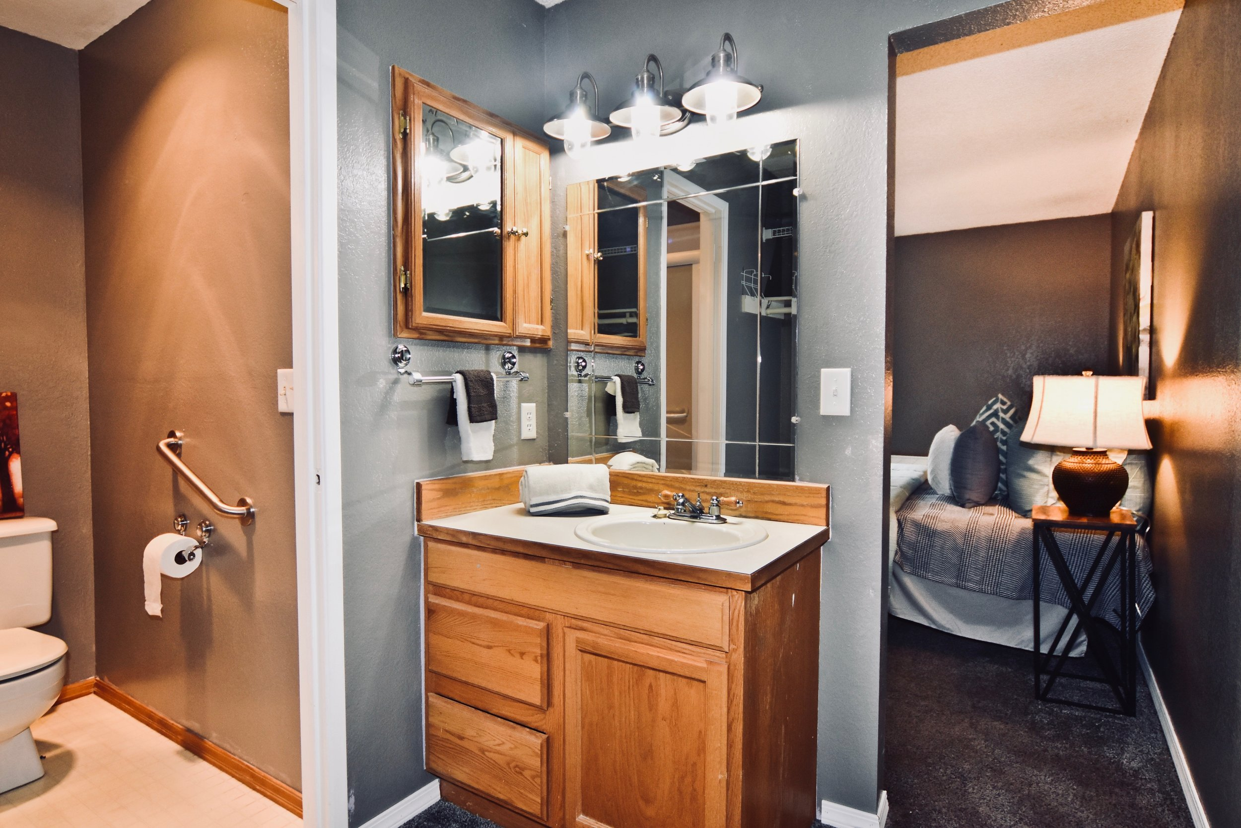 Ensuite bathroom vanity + additional closet space behind leading to shower area.