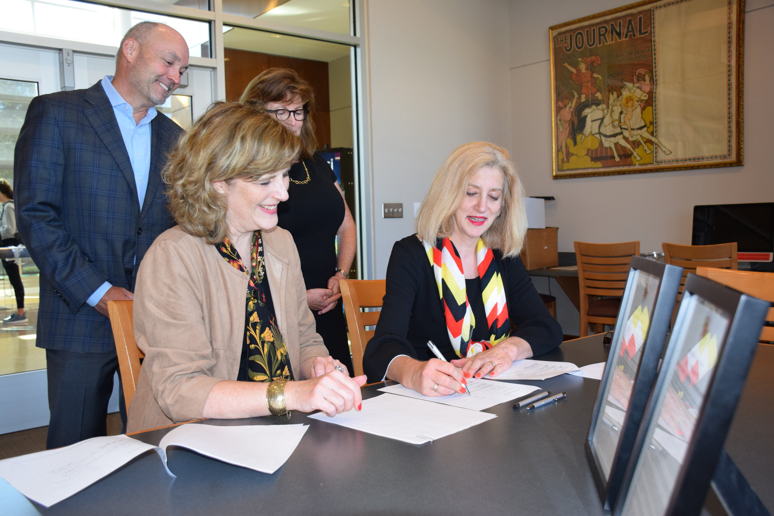 Lucy A. Dalglish (left), dean of the University of Maryland Philip Merrill College of Journalism, and Andrea Chamblee ('83) sign an agreement in the Gaylord Library of John S. and James L. Knight Hall to establish a scholarship in honor of John McNamara ('83) as friends watch in the background. (Photo courtesy of Alexander Pyles)