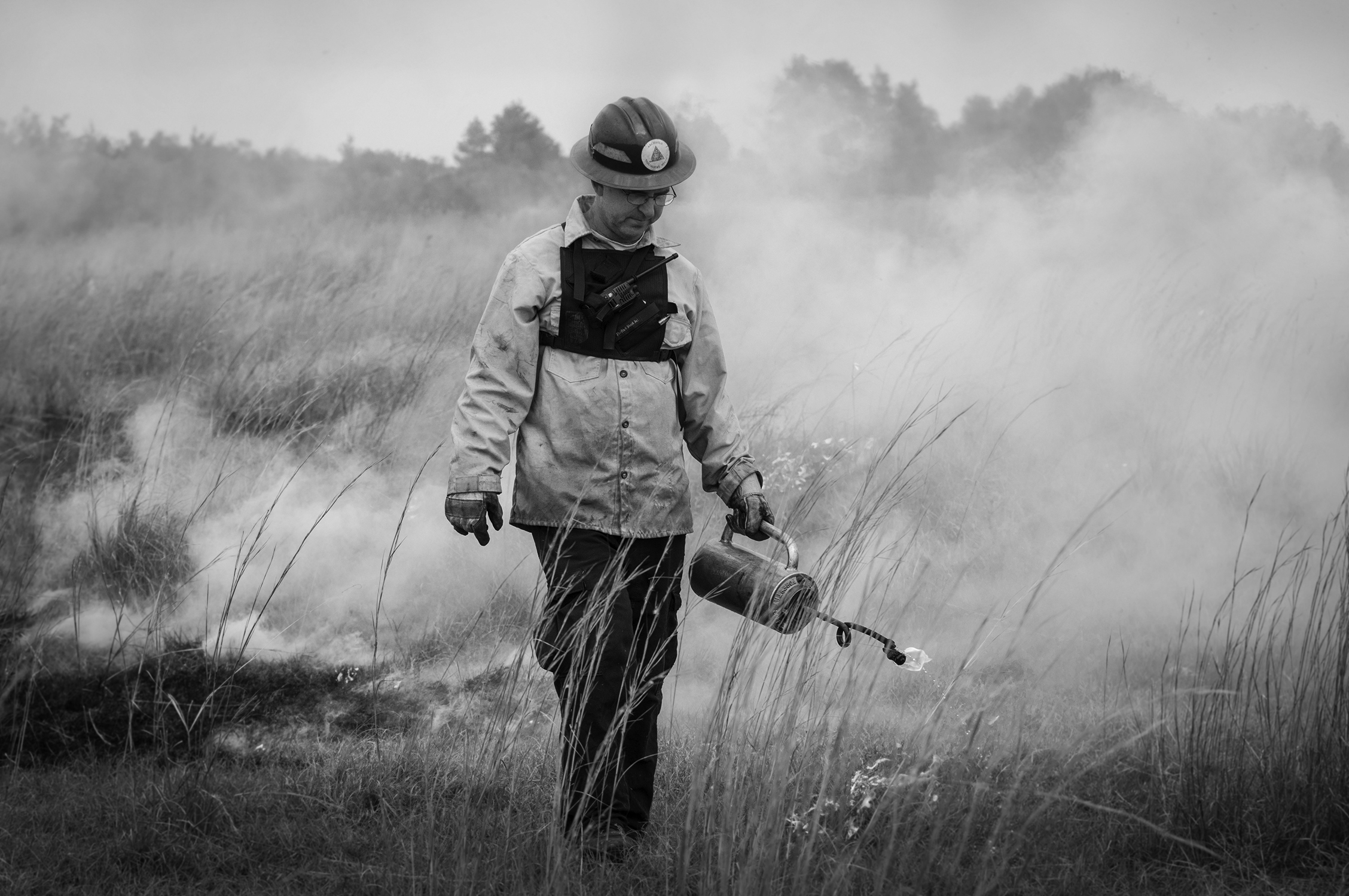 Land Manager, Kevin Main uses a driptorch during a prescribed fire as part of a habitat restoration project at Archbold Reserve.