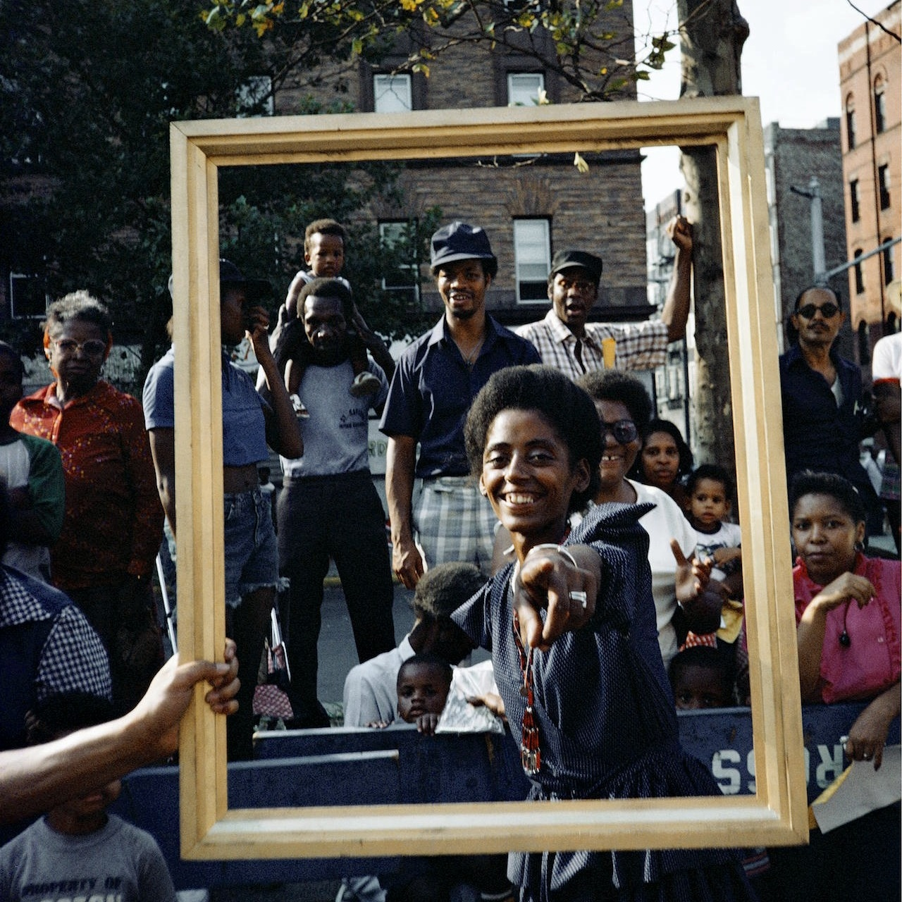 1983 - Celebrated artist Lorraine O'Grady challenges main stream to re-think perceptions of Blackness by transforming a float into a moving gold post. Standing on it were various African American male & female dancers holding gold frames. Her work was recently featured at the Harlem Studio Museum, more than three decades later