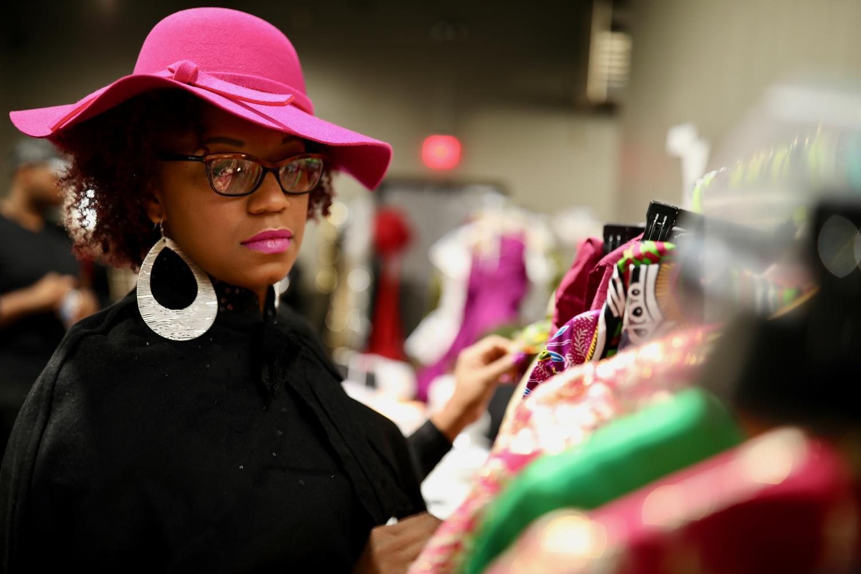 Kenya Buchanan examines her collection of original clothing backstage at Magic City Fashion Week. CW/ Joe Will Field