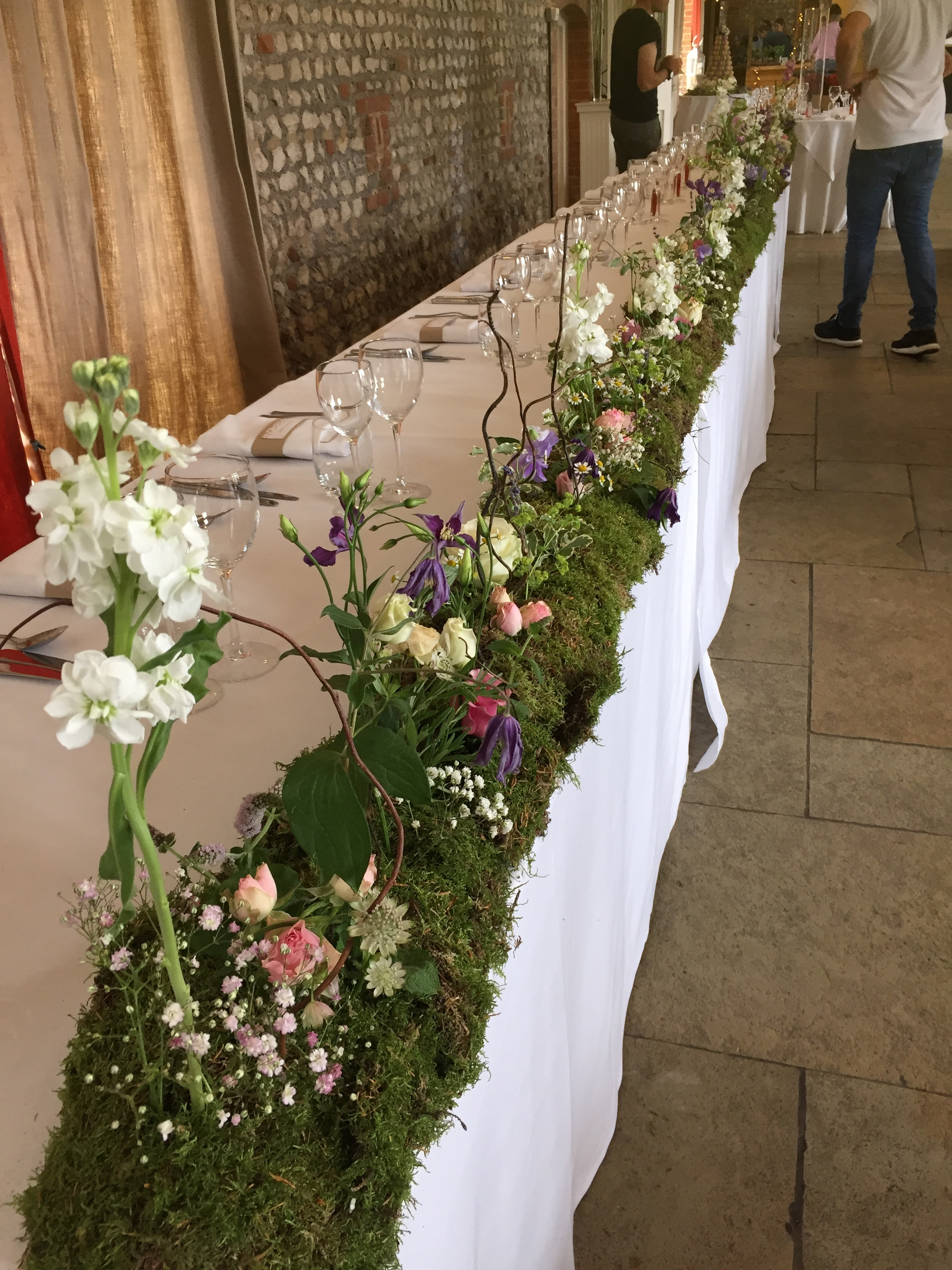 We created a moss runner the entire length of the Top Table and 'planted' a mixture of flowers and herbs to create a wild garden.