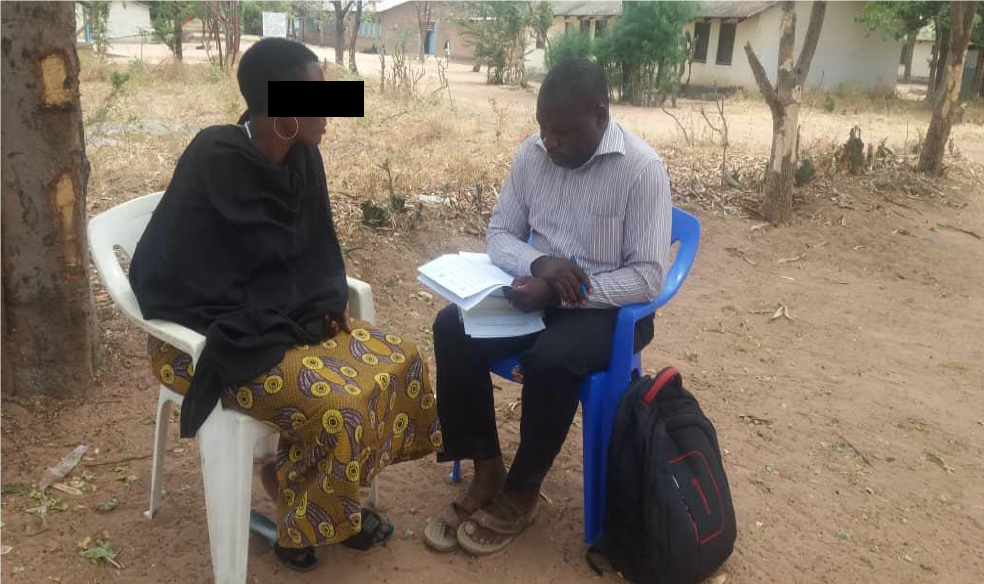 A Research assistant administering a quantitative questionnaire to a female participant at Kigongo village