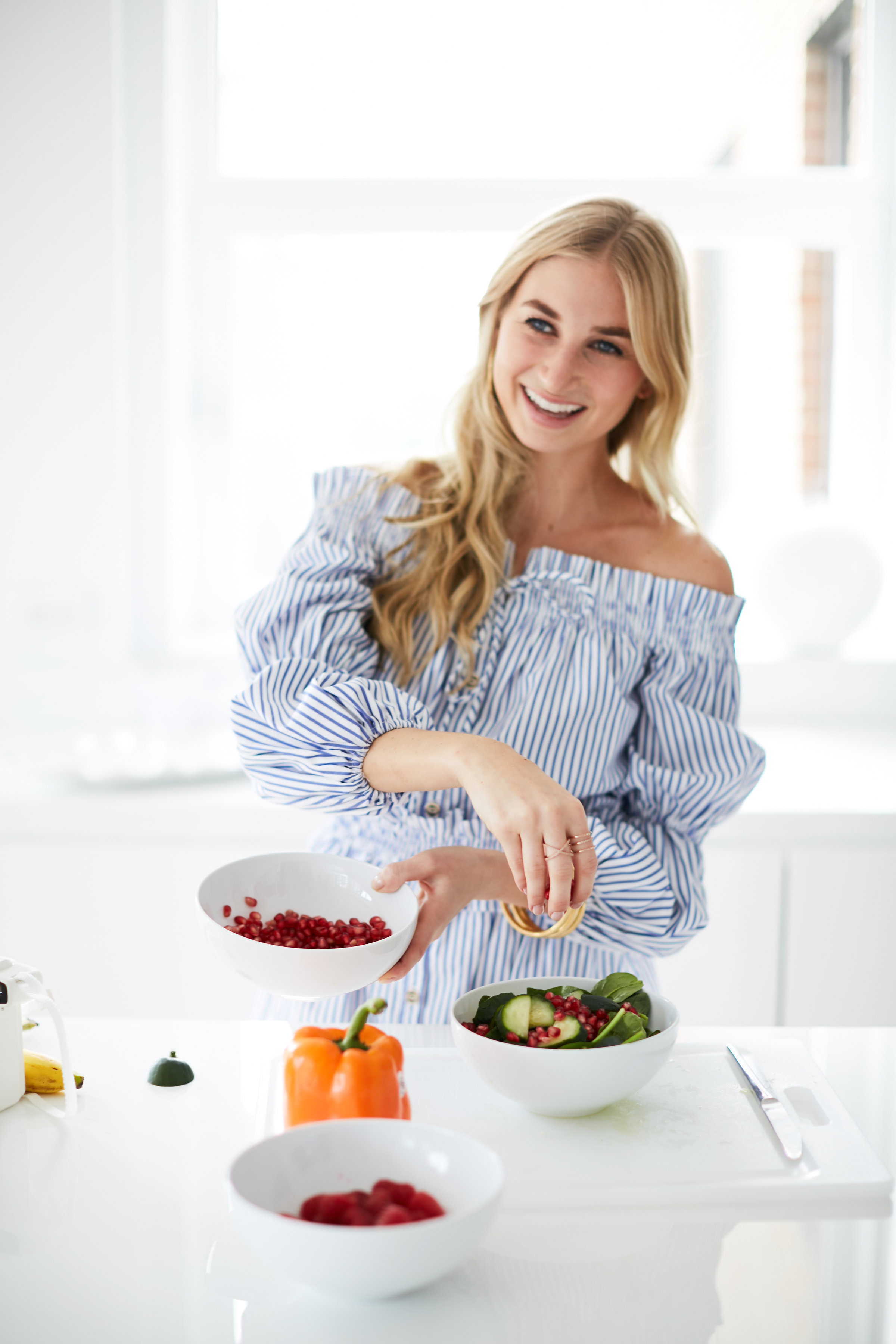 blonde woman in blue shirt smiling preparing salad