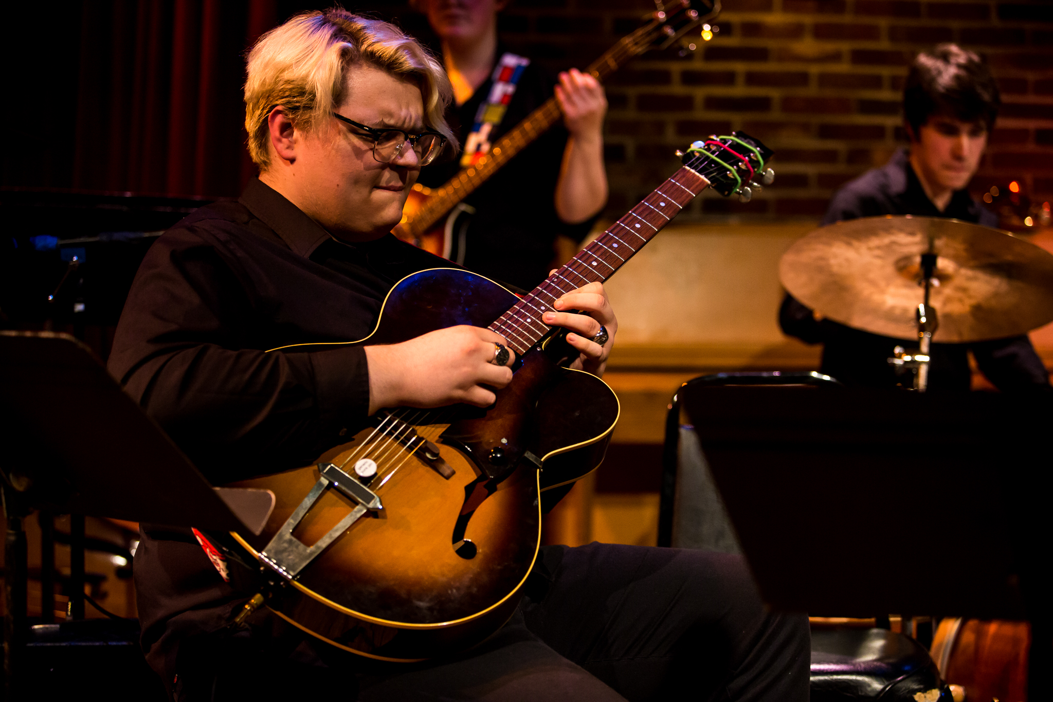 This rhythm section of guitar, bass, and drums works together to provide a solid groove on stage at the Union Cabaret and Grille in February 2019.