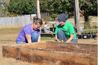 Corina Common and Jennifer Walker constructraised beds at the community garden in Metcalfe County.