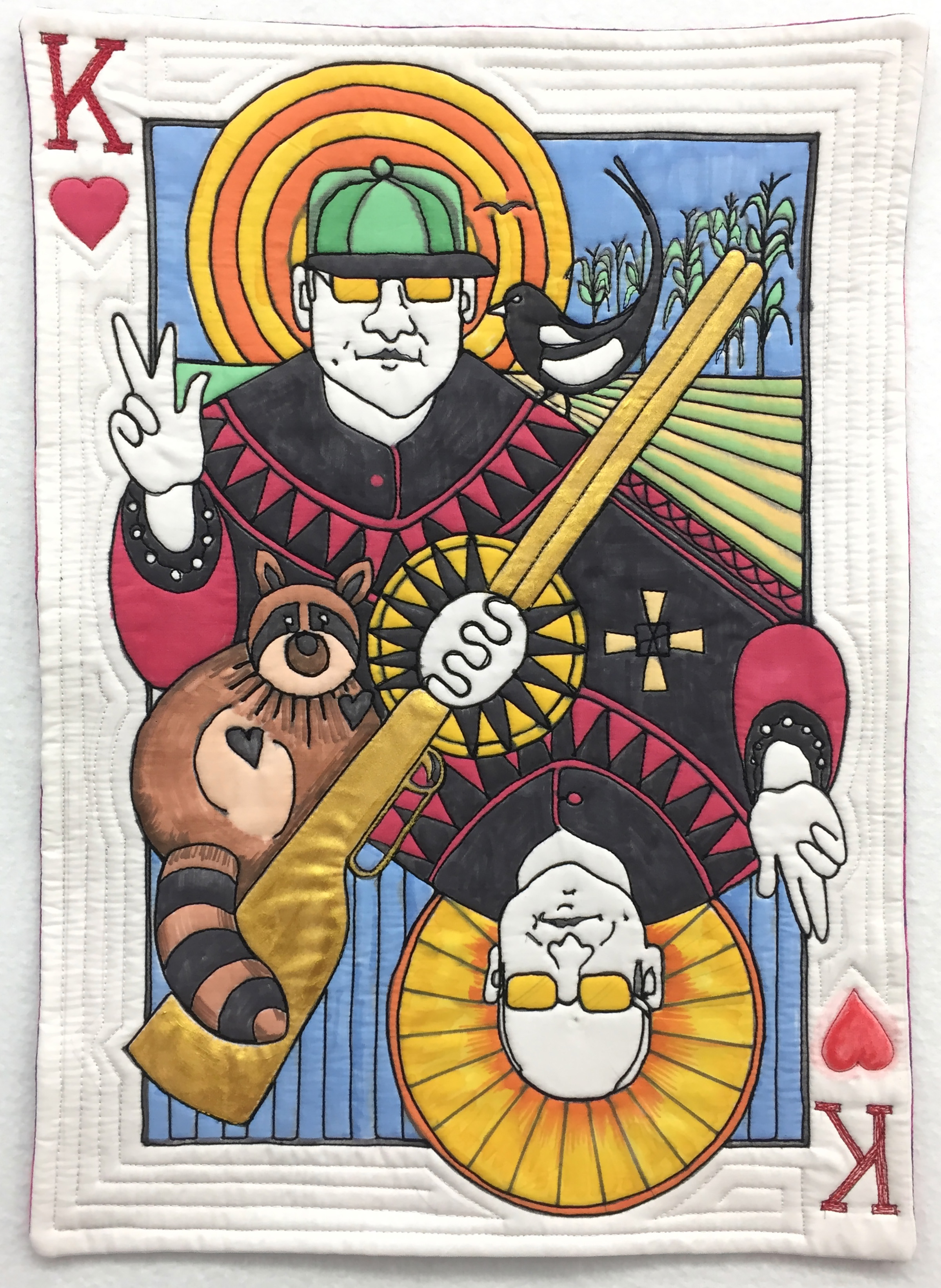 """The King of HEarts - 12"""" x 18"""" – Feb 2019He's a card – the King of Hearts!The host and guardian of Art Quilt Campus held annually at St. Peter's College in Muenster, Saskatchewan, is Father Demetrius - the king of my heart. He is a completely endearing man, serious and spiritual on one side, funny and whimsical on the other. I've depicted these traits along with my interpretation of him as The Protector of Corn, this from a memorable account of his efforts to keep raccoons and magpies from his cornfields."""