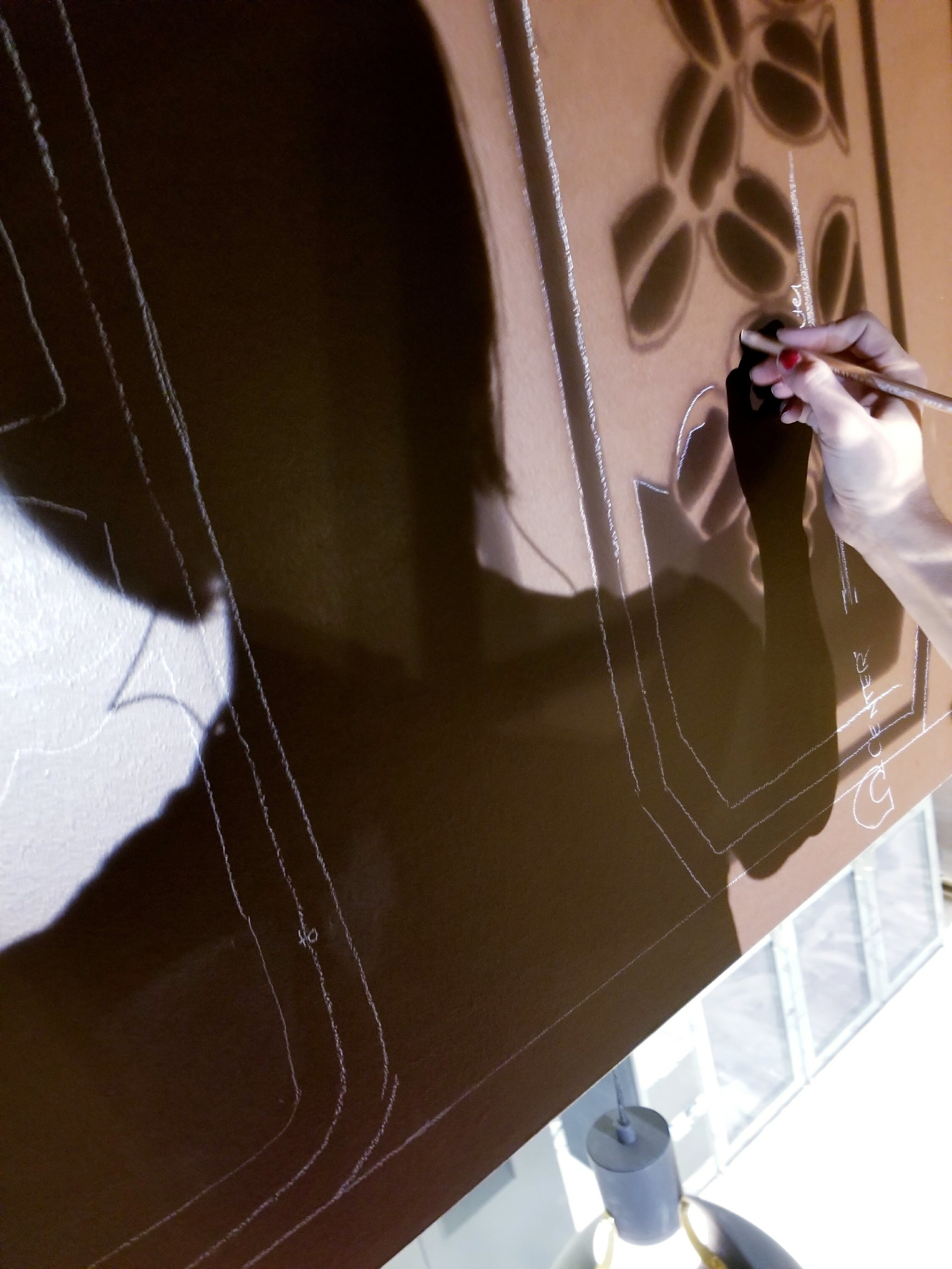 Projecting and tracing the outlines of the design onto the wall