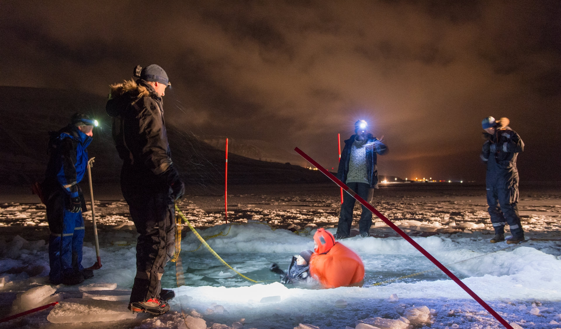 Every year, UNIS educates hundreds of students in Arctic safety. As part of the winter field safety course, students must swim through ice-filled water and manage to get back up onto the sea ice again. Photo: Frede Lamo / UNIS