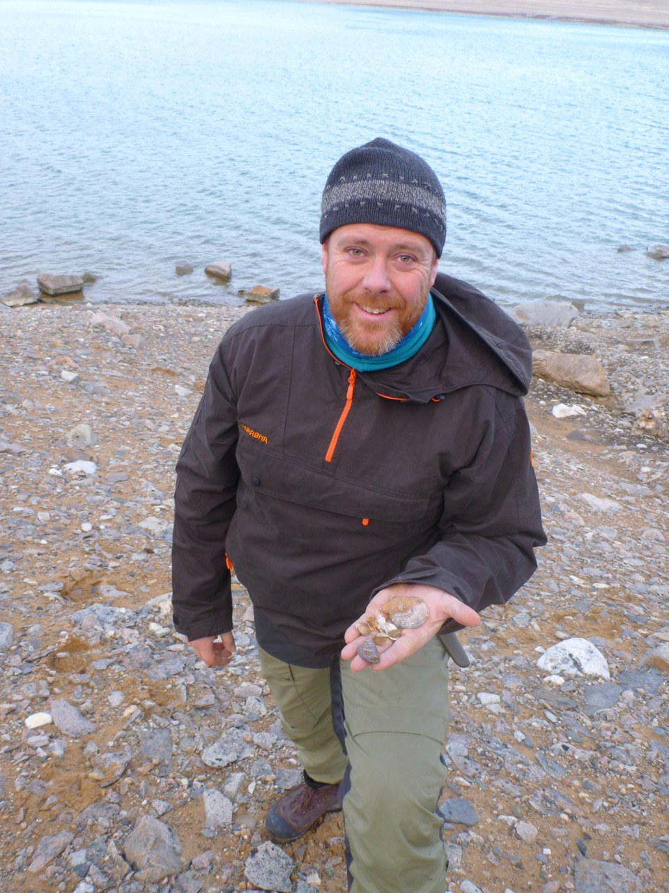 The author with fossil shells from Rijpfjorden in Svalbard. Mussels lived in Svalbard in warm periods after the last Ice Age, but which species lived here then? It has not been possible to isolate DNA from these fossils. Photo: Colin Griffiths / SAMS