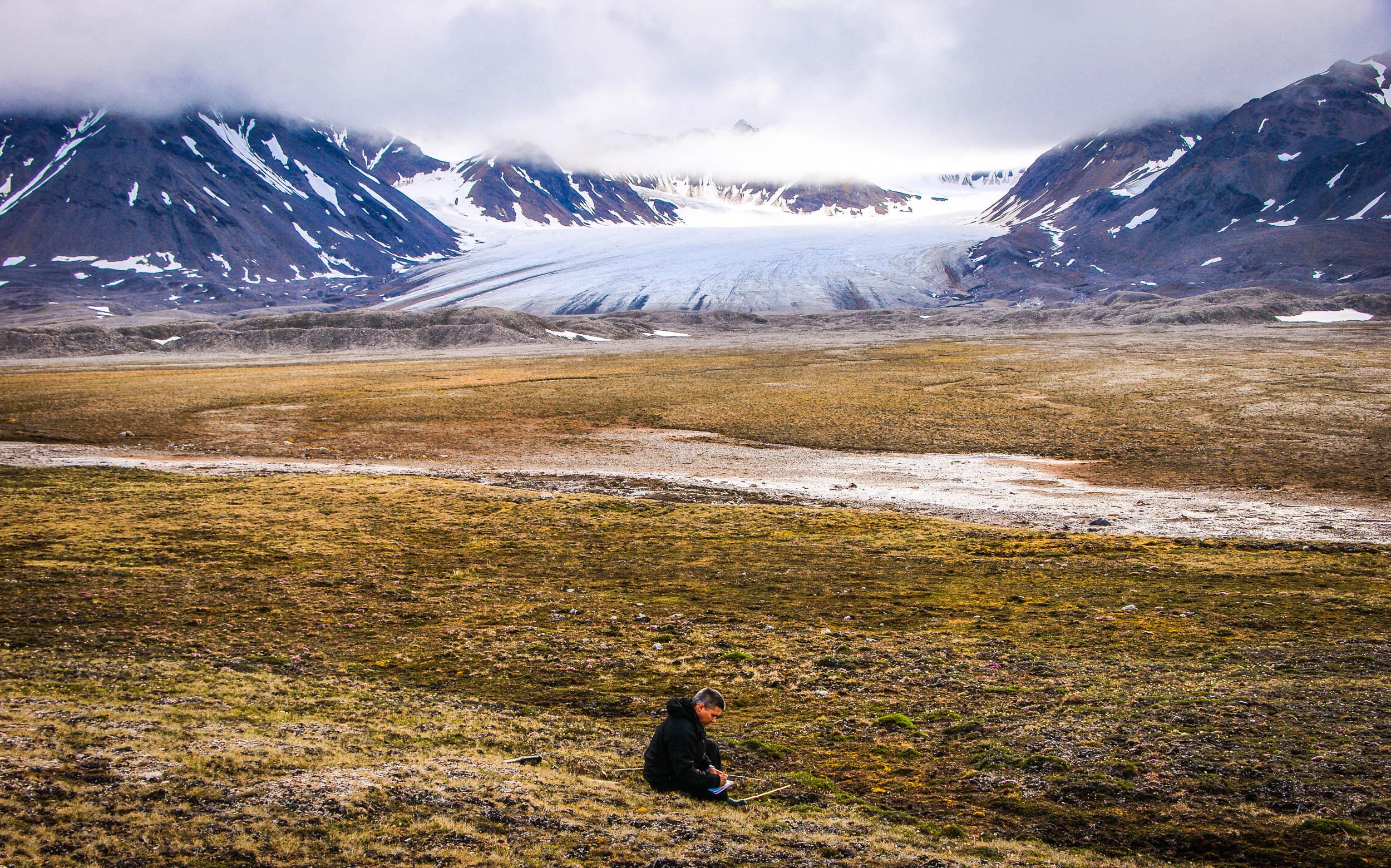 Jarle W. Bjerke doing research work with Vestre Brøggerbreen glacier in the background.  JONAA©Trond Johnsen