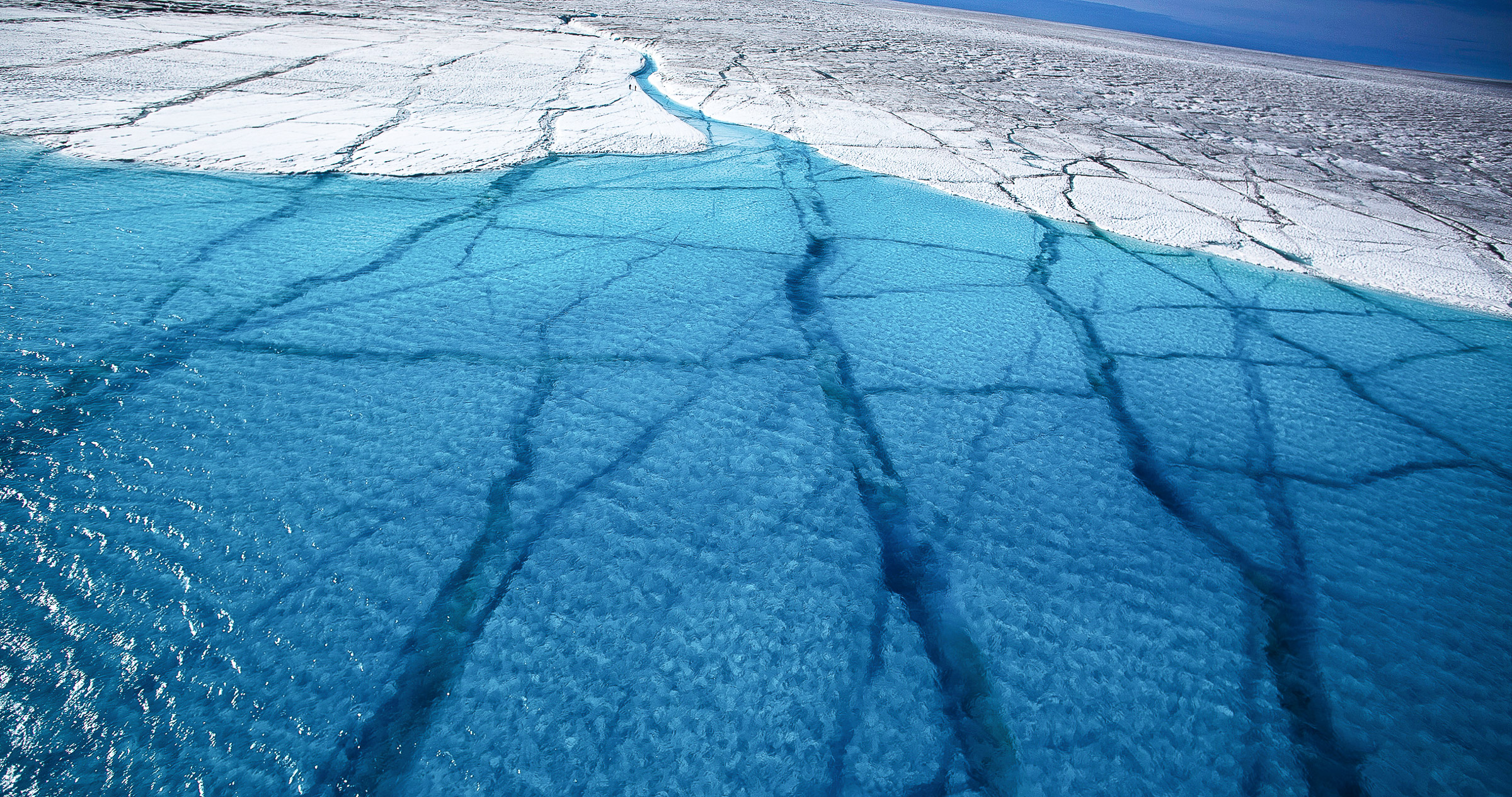 Increased surface melt allows flowing water to travel deeper into the ice causing more melt, as this lake on Greenland's icecap shows clearly.   JONAA©Ragnar Axelsson