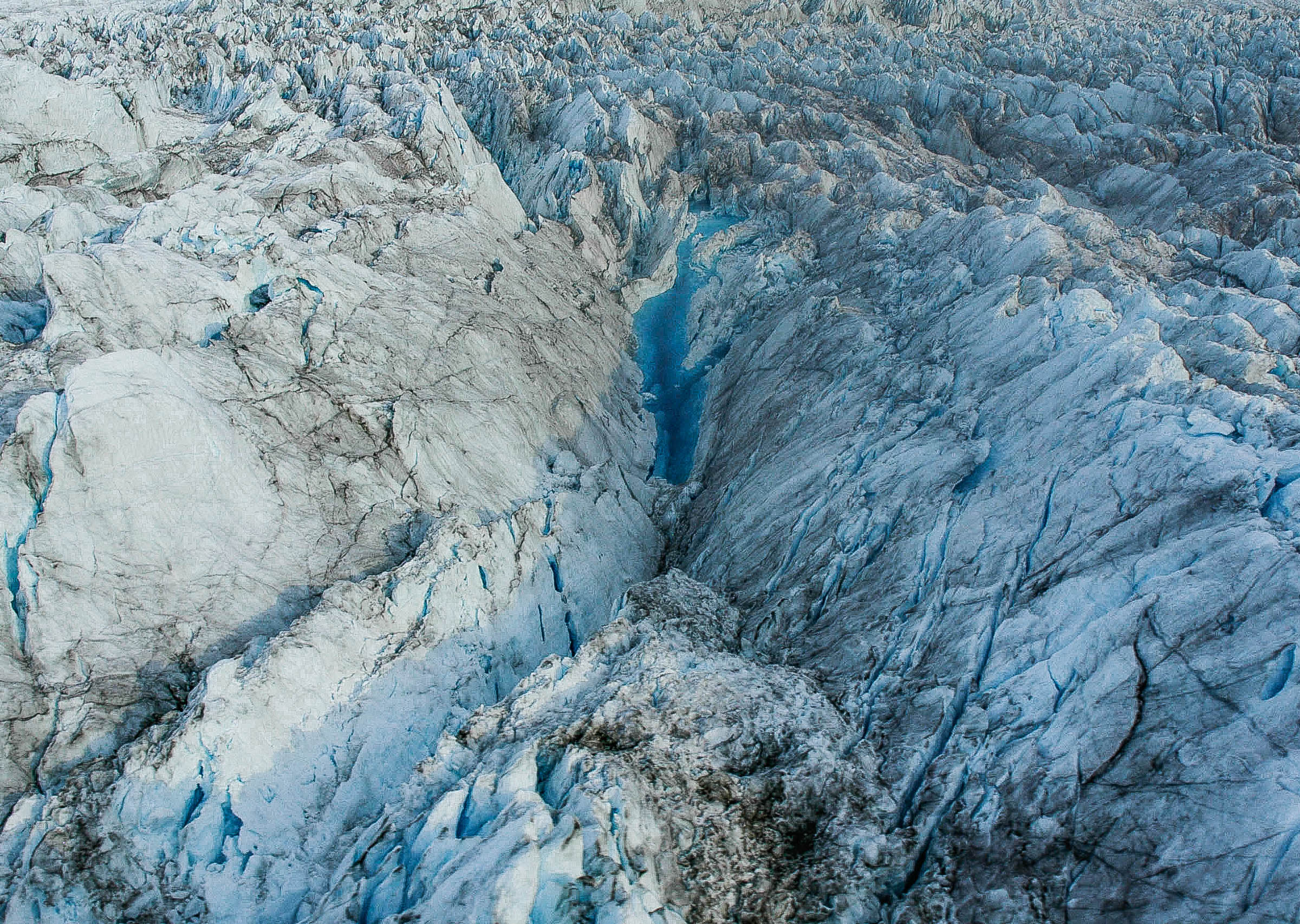 Melted surface ice finds its way as water into a glacier through cracks and crevasses, weakening the ice and  accelerating  glacier retreat. Photographed in Greenland. JONAA©Kristjan Fridriksson