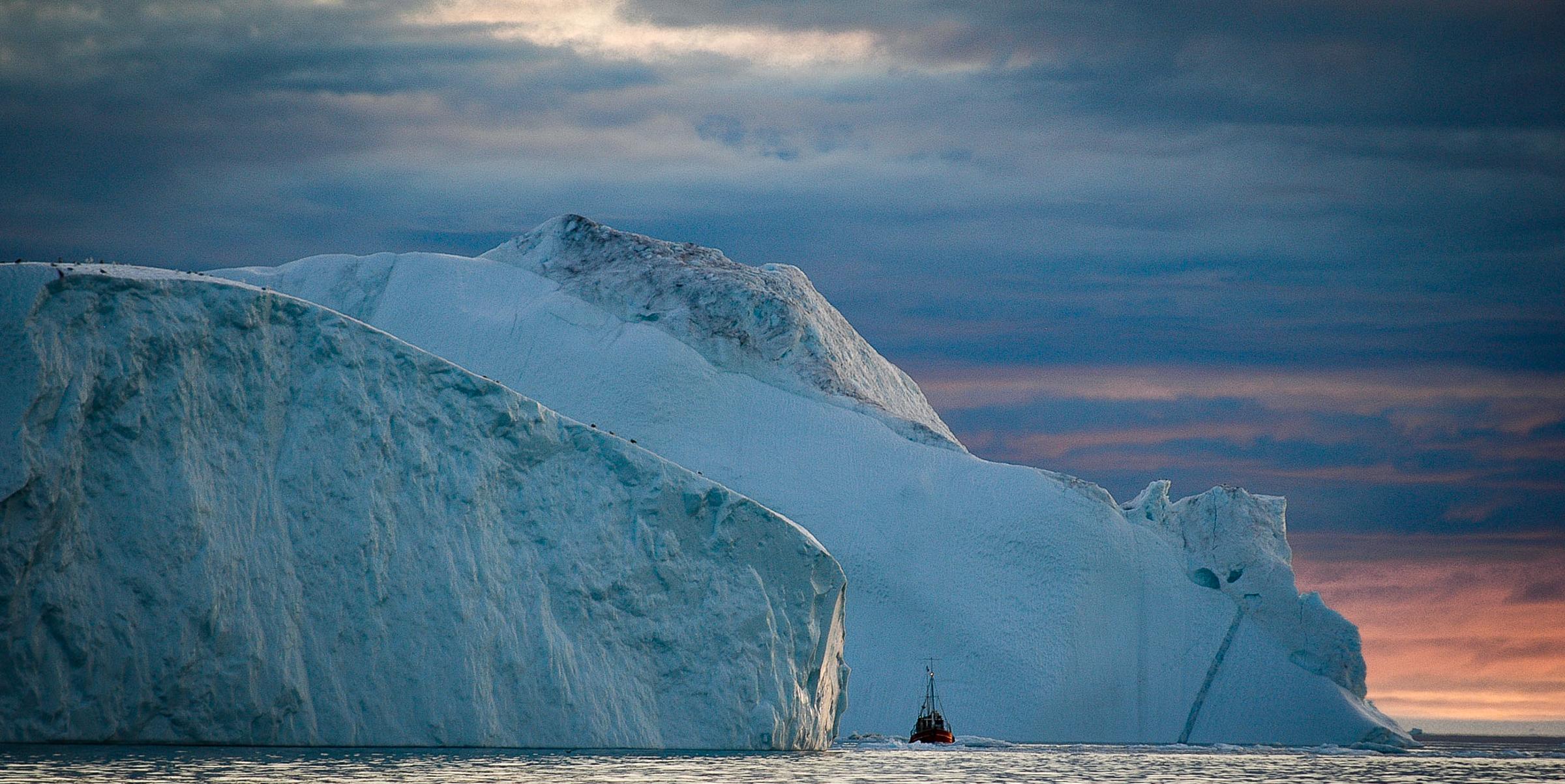 Sailing out of the iceberg cluster under the midnight sun.  JONAA©Kristjan Fridriksson