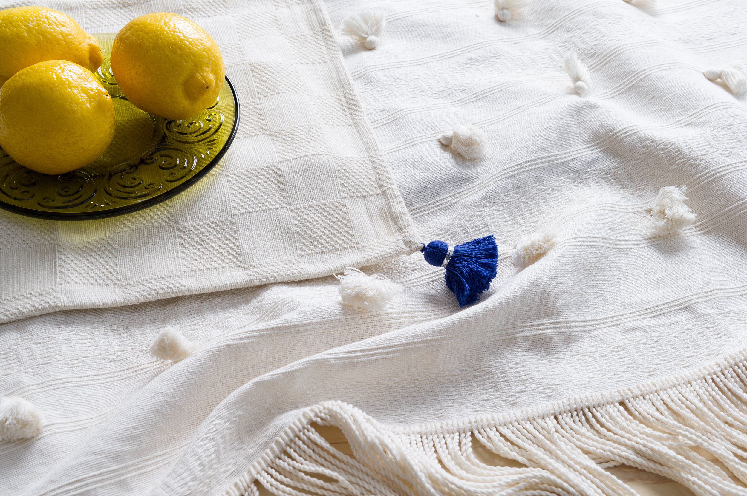 100% organic cotton Tassel Napkin on top of the Tassel Blanket made in by our artisan partners in Mexico.