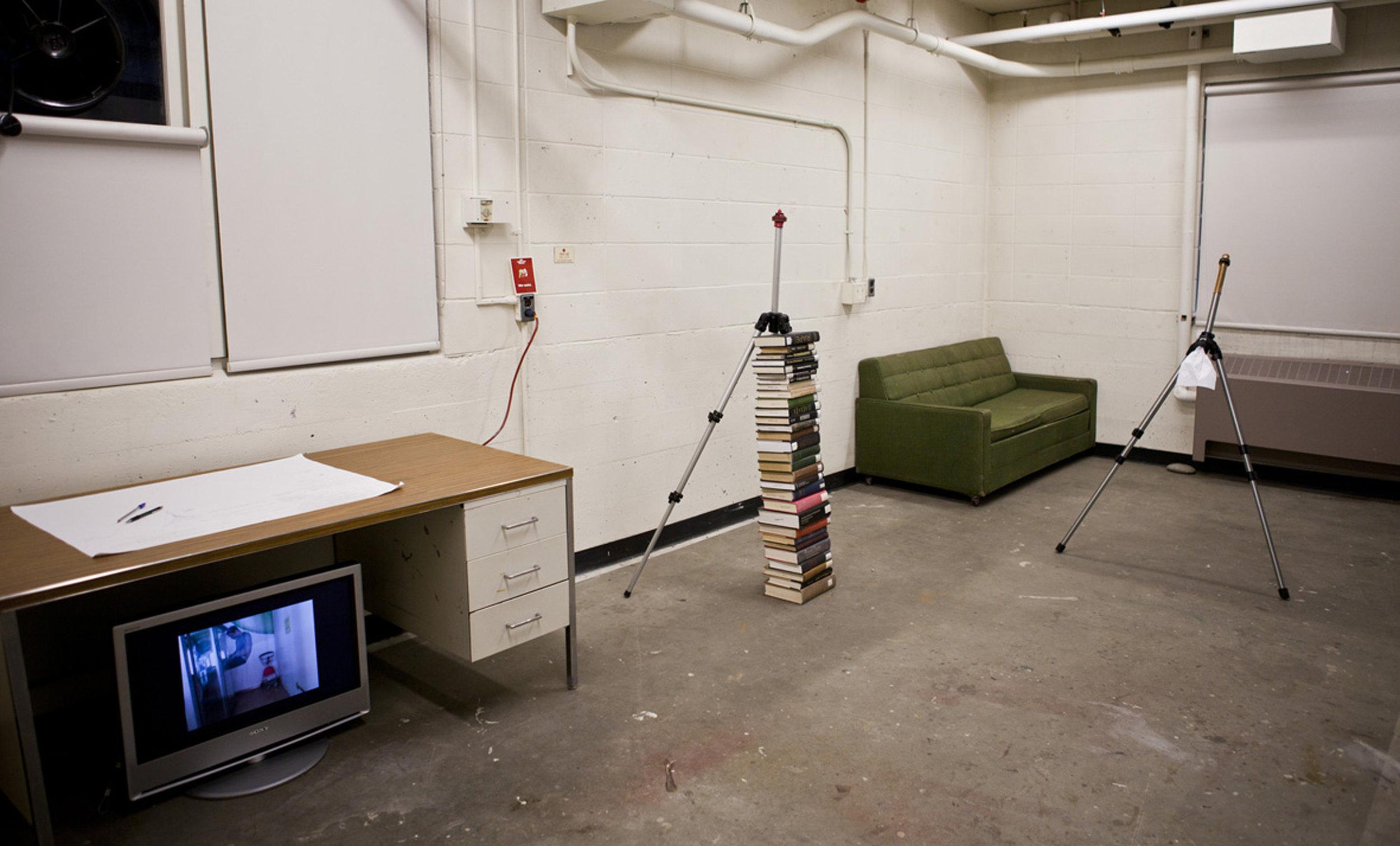 aluminum tripod, book, latex condom, working table, digital monitor, single channel video (Installation view)