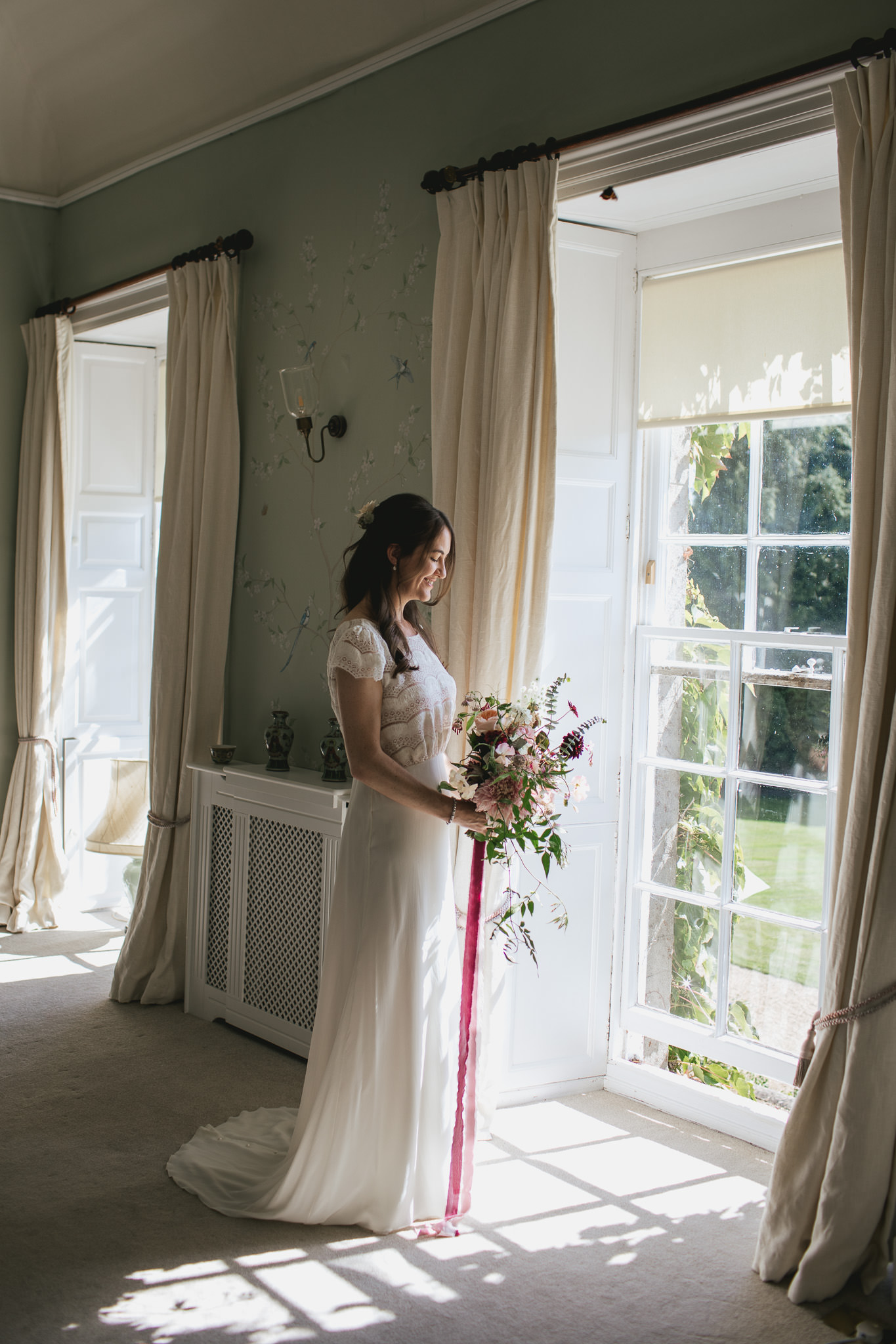 Outdoor wedding at Pennard House, Somerset_bride holds bouquet by window