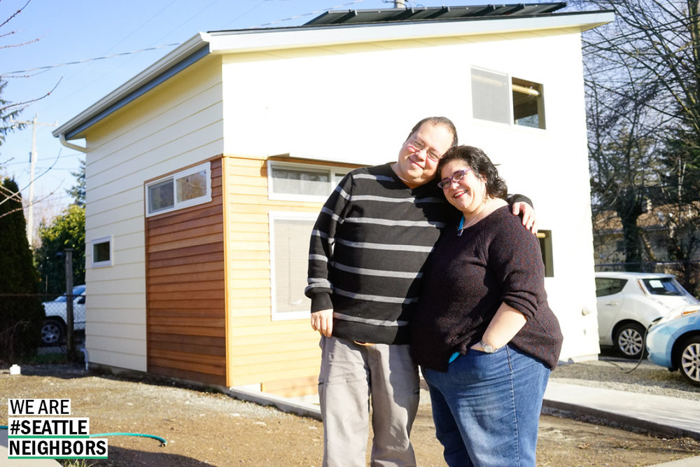 Kay and  her husband stand in front of their backyard cottage built for her brother.