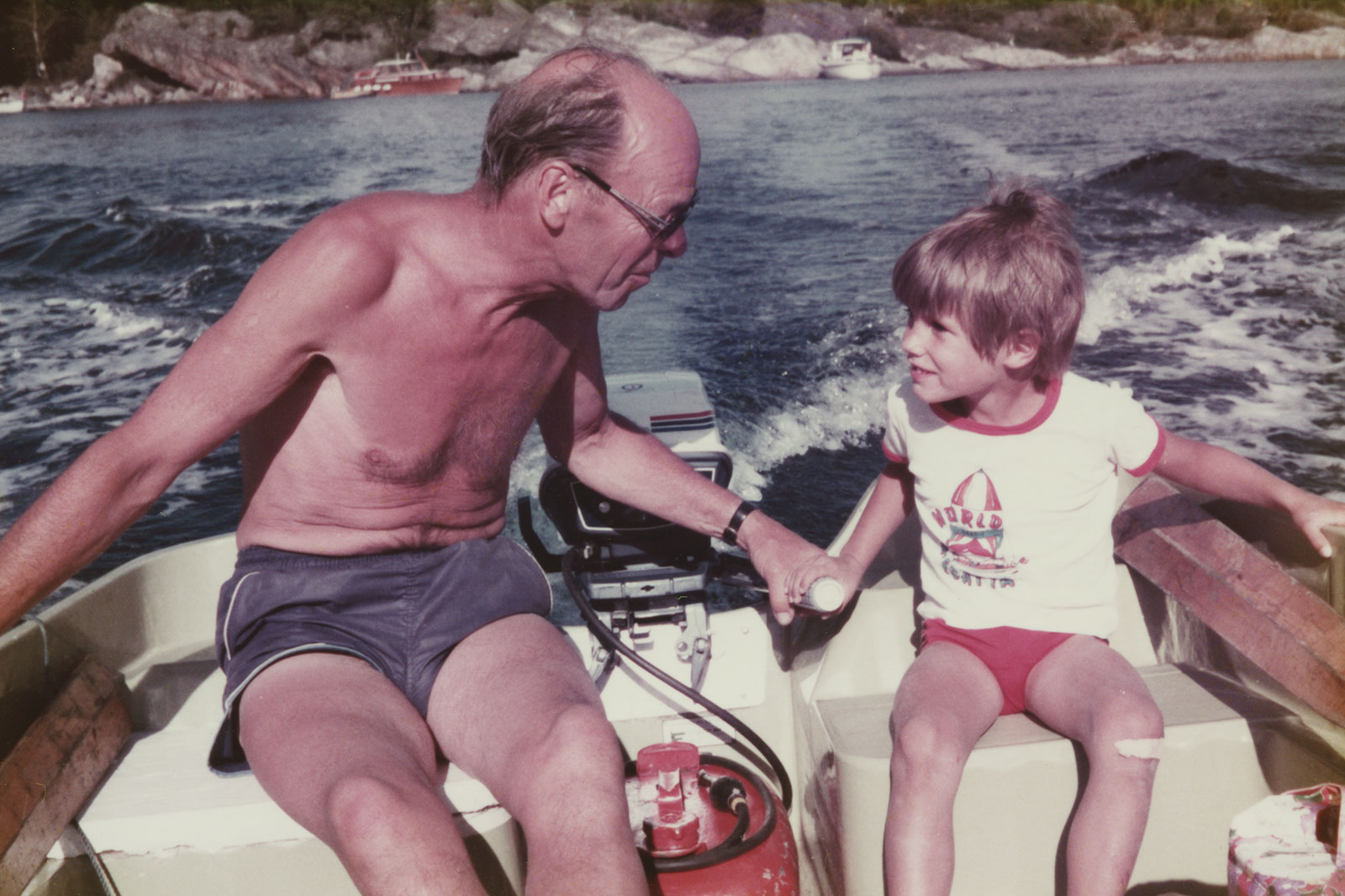 Grandfather Arvid teaching Christopher to steer the boat. Ca. 1984.