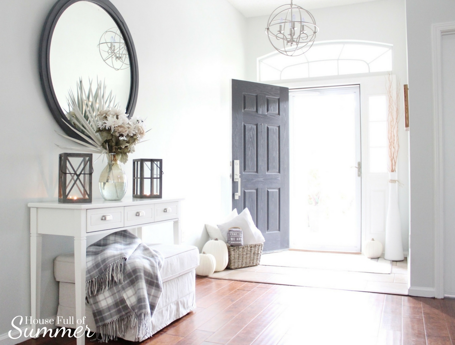 House Full of Summer: Fall Home Tour Blog Hop - Cozy, Coastal, Chic Foyer fall decorating ideas. Neutral interior, white pumpkins, front door decor, white console table, plaid throw, faux fall florals, entryway ideas, wood floors, orb chandelier, round mirror, lanterns, coastal fall, tropical fall, palm fronds