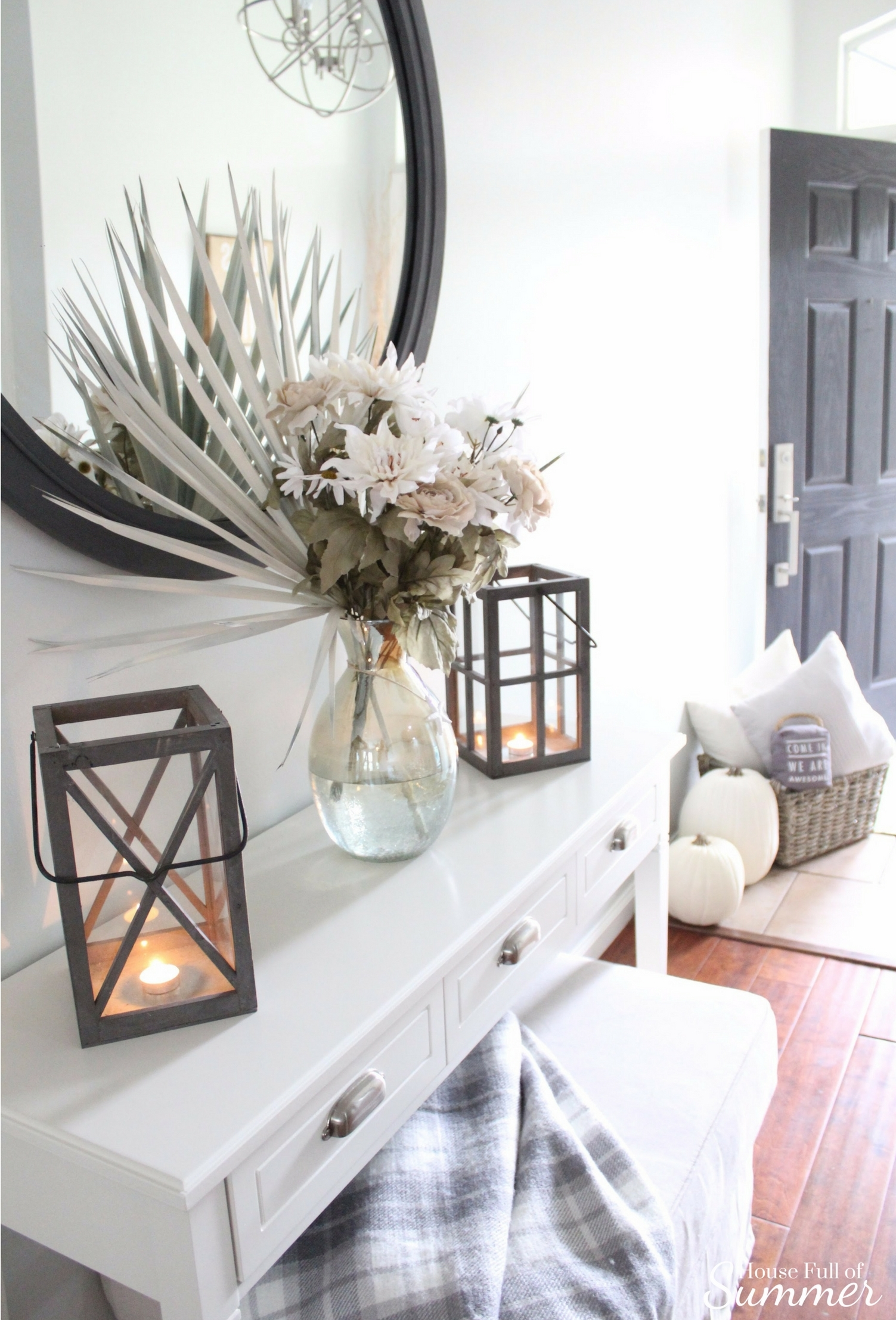 House Full of Summer: Fall Home Tour Blog Hop - Cozy, Coastal, Chic Foyer fall decorating ideas. Neutral interior, white pumpkins, front door decor, white console table, plaid throw, faux fall florals, entryway ideas, wood floors, orb chandelier, round mirror, lanterns, coastal fall, tropical fall, palm fronds, diy ideas