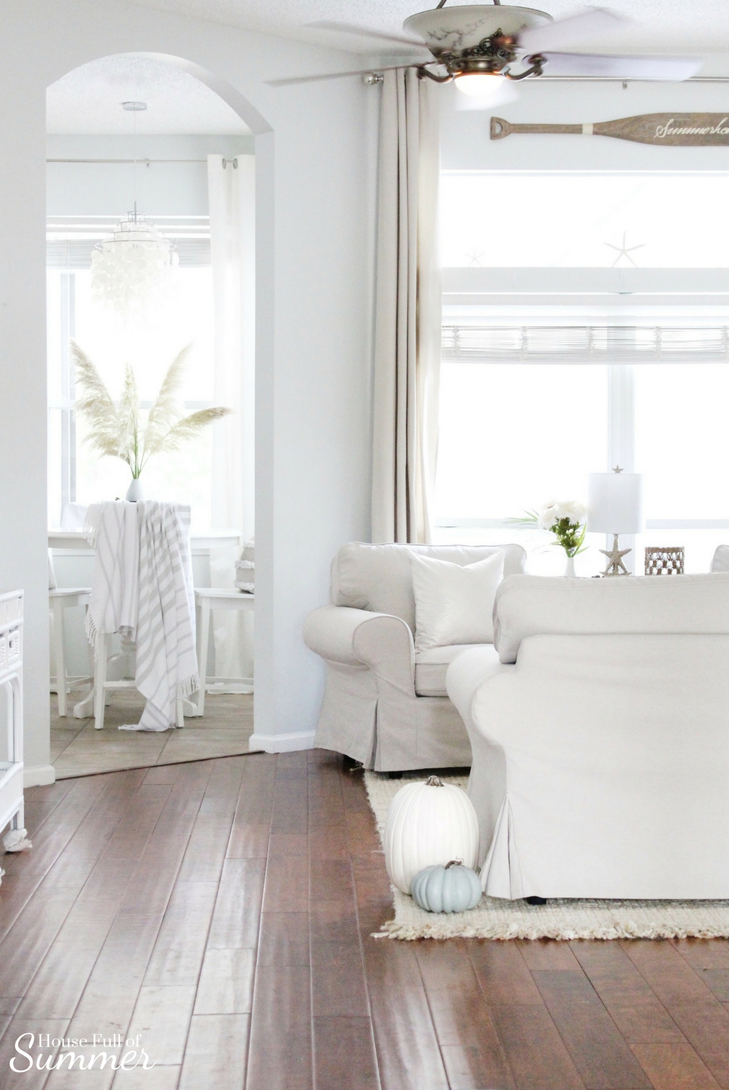 House Full of Summer: Fall Home Tour Blog Hop - Cozy, Coastal, Chic Living Room fall decorating ideas. Neutral interior, living room decor, white pumpkins, blue pumpkins, beige living room ideas, striped throw, breakfast nook, white chandelier