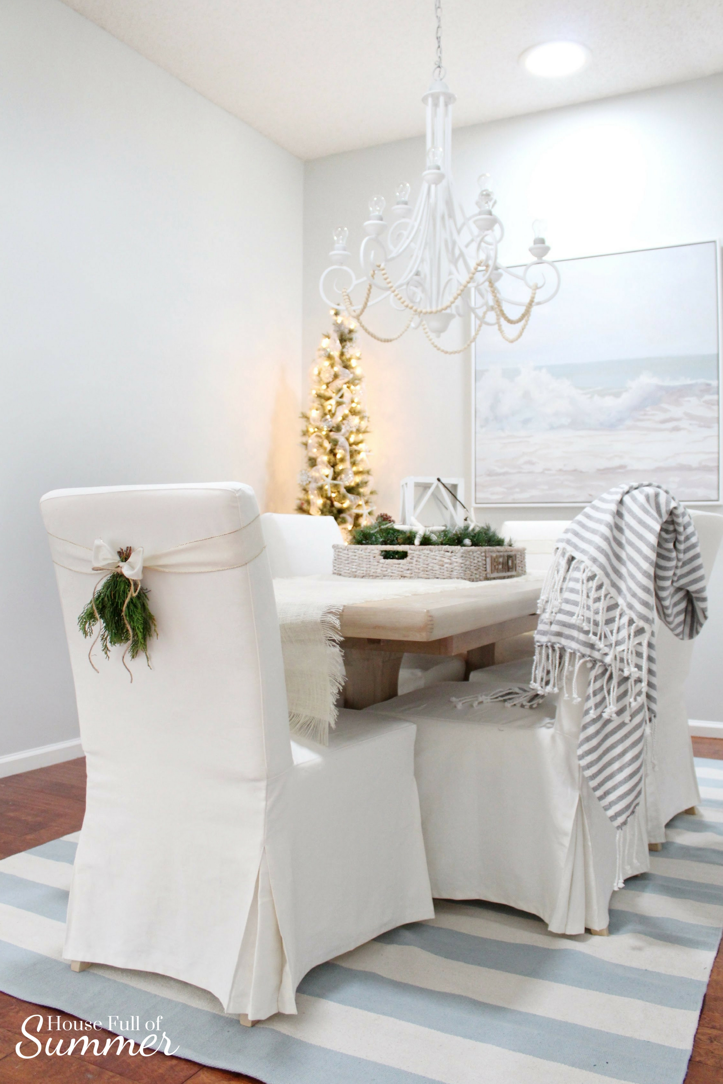 Christmas Home Tour | House Full of Summer blog hop - Cheerful Christmas Home Tourcoastal christmas neutral christmas decor, holiday home tour, florida christmas, white dining room, chair swag, christmas centerpiece, white chandelier, pencil tree, blue and white coastal Christmas decor, neutral coastal decor, beachy Christmas dining room