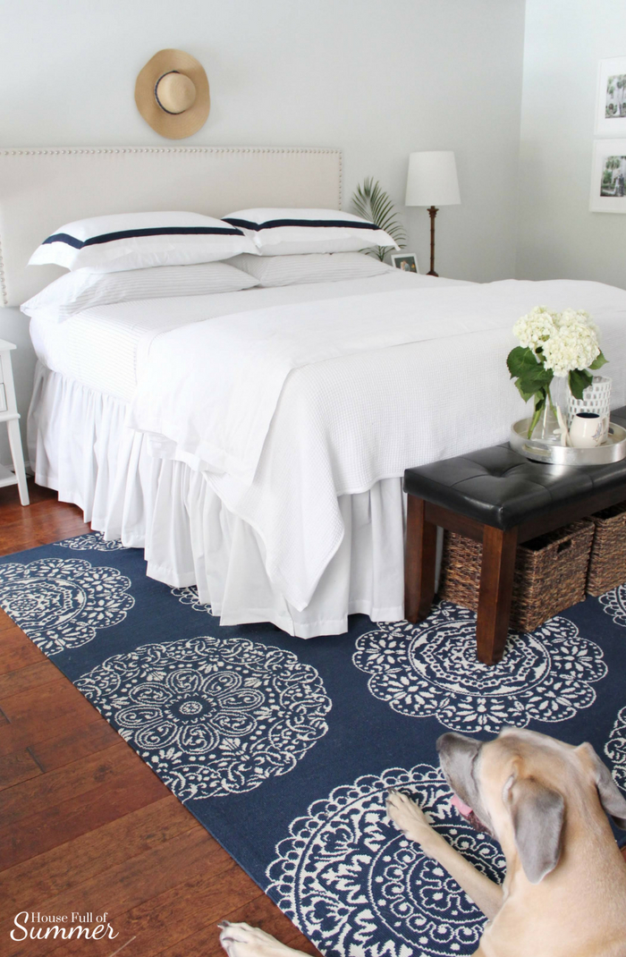 Casual Coastal Summer Bedding | House Full of Summer - nautical and coastal vibes in a blue and white bedroom. Boll & Branch duvet and navy ticking sheets, hotel bedding, beige nailhead headboard upholstered, extra long drop bed skirt, bamboo lamps, tropical accents, navy medallion rug. Sherwin Williams Fleur de Sel paint color