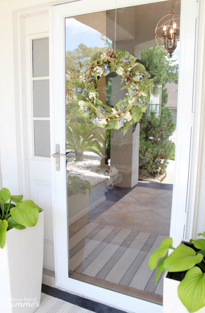 Self-Watering Planters and a Stylish Front Porch | House Full of Summer - front porch decor, white tall planters, summer front porch, summer decor, coastal home exterior, white porch, Florida home, natural dried wreath with hydrangeas Jackson & Perkins #housefullofsummer