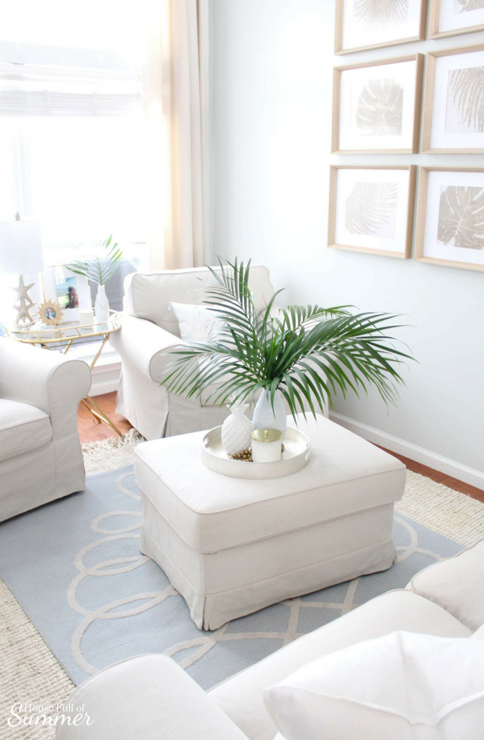 Serene Coastal Chic Living Room Decor | House Full of Summer coastal home interior, Palm Beach chic style, elegant coastal living room ideas, blue and beige interior, slipcovered furniture, palm fronds, Florida home style, tropical decor, layered rugs, natural rug, gallery wall, coastal wall decor, #housefullofsummer