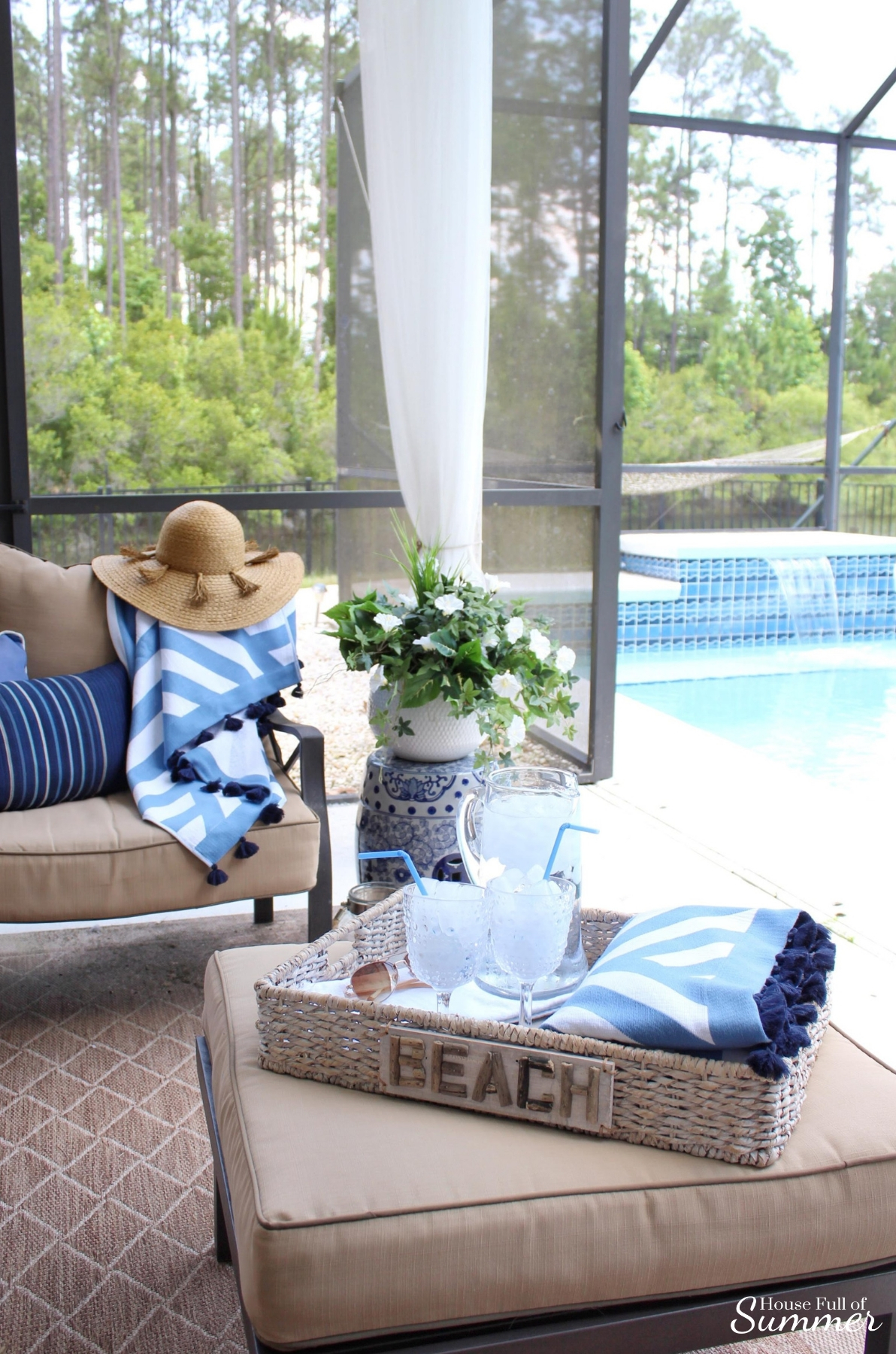 Blue & White Poolside Retreat | House Full of Summer - Serena & Lily beach towels, patio decor, outdoor living room, cozy patio, chinoiserie chic garden stool, coastal home decor, Florida home, lanai, beach accessories, Summer decor, striped towels, tassels
