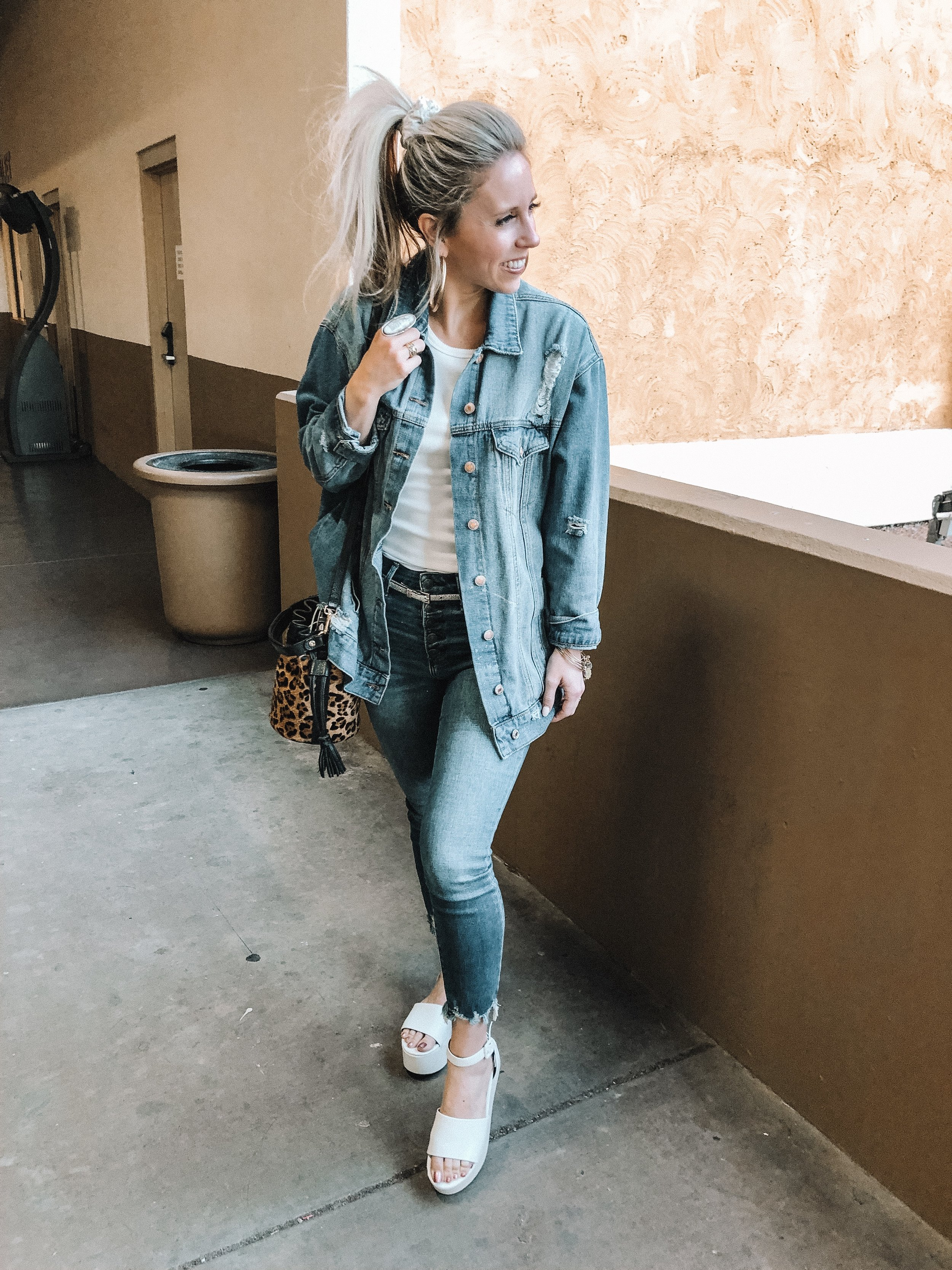 Denim trend featured by top US fashion blog, Life of a Sister: image of a woman wearing a distressed denim jacket