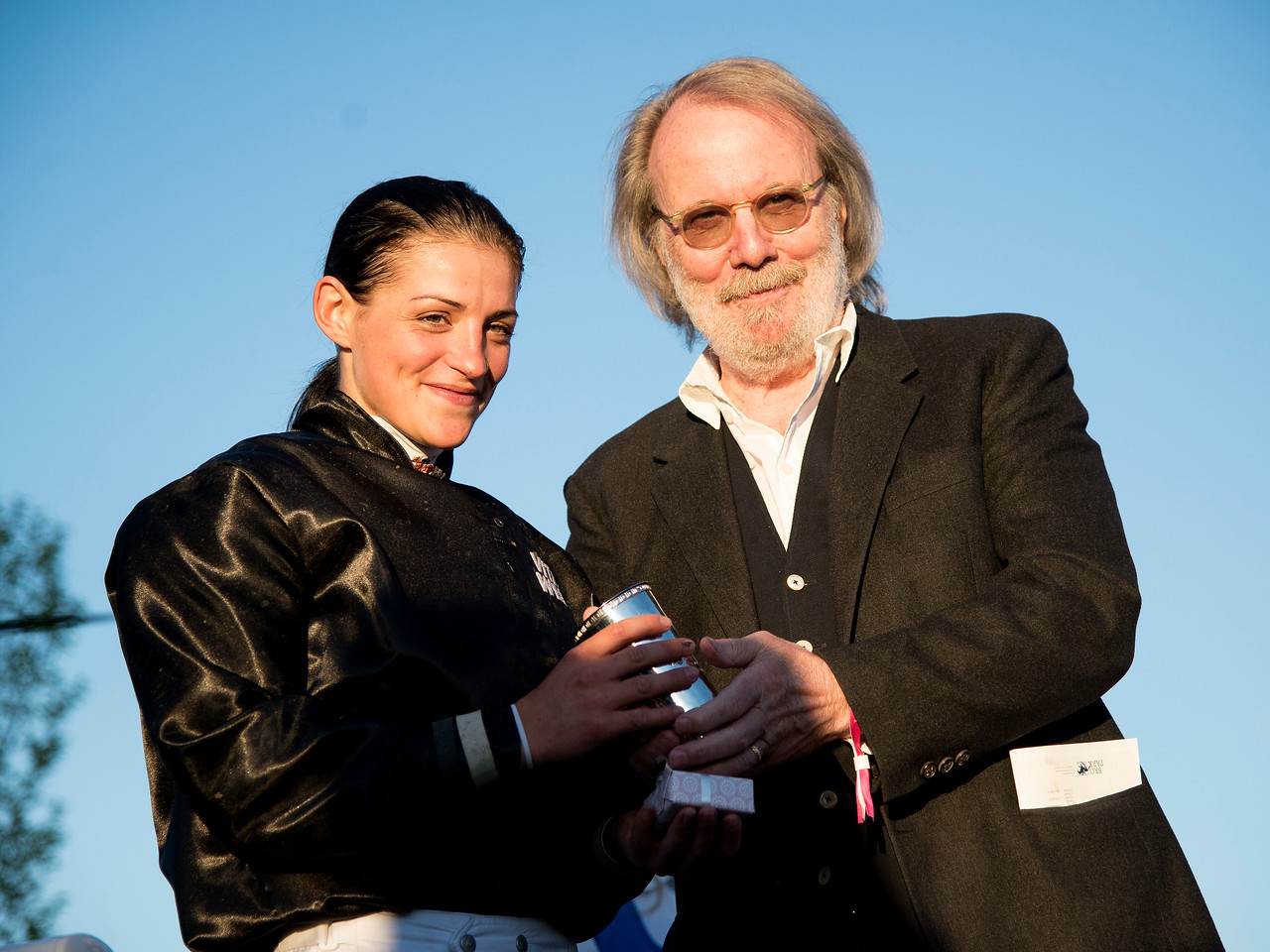 Maryline Eon, the winner of the Lady Jockeys' Thoroughbred World Championship, receives the trophy from the event sponsor Benny Andersson.