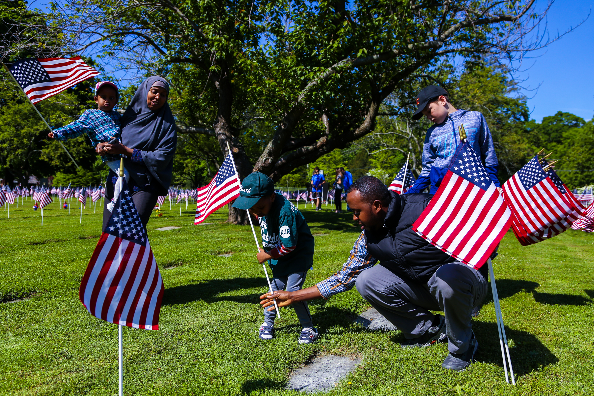Nur Ali , 4, and his father place flags on veterans' graves as his family watches. May 25, 2019, at Cambridge Cemetery in Cambridge, Massachusetts. ( The Cambridge Chronicle )