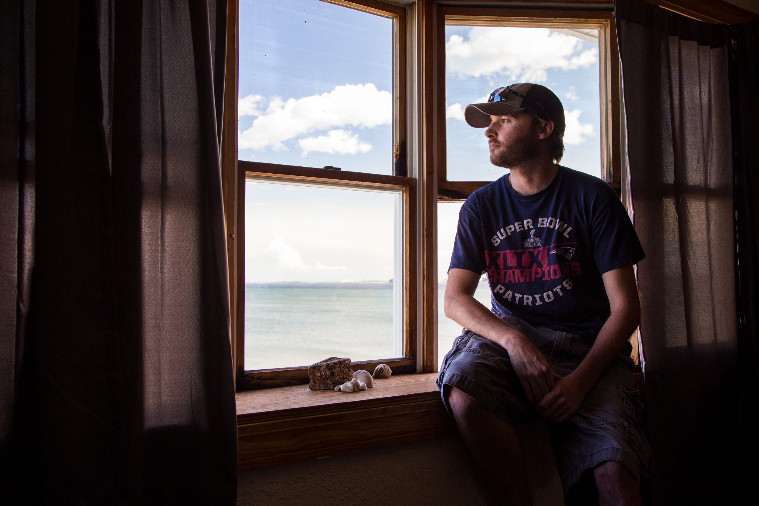Rideshare driver  Jeff Carpenter , 30, a recovering alcoholic, gazes at the beach from his apartment window. June 22, 2019. in Revere, Massachusetts.