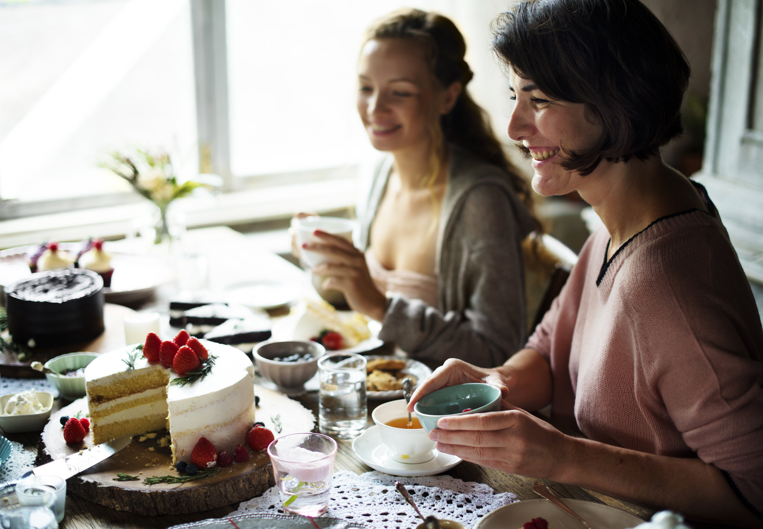 Two women drinking tea sitting at a table with cakes