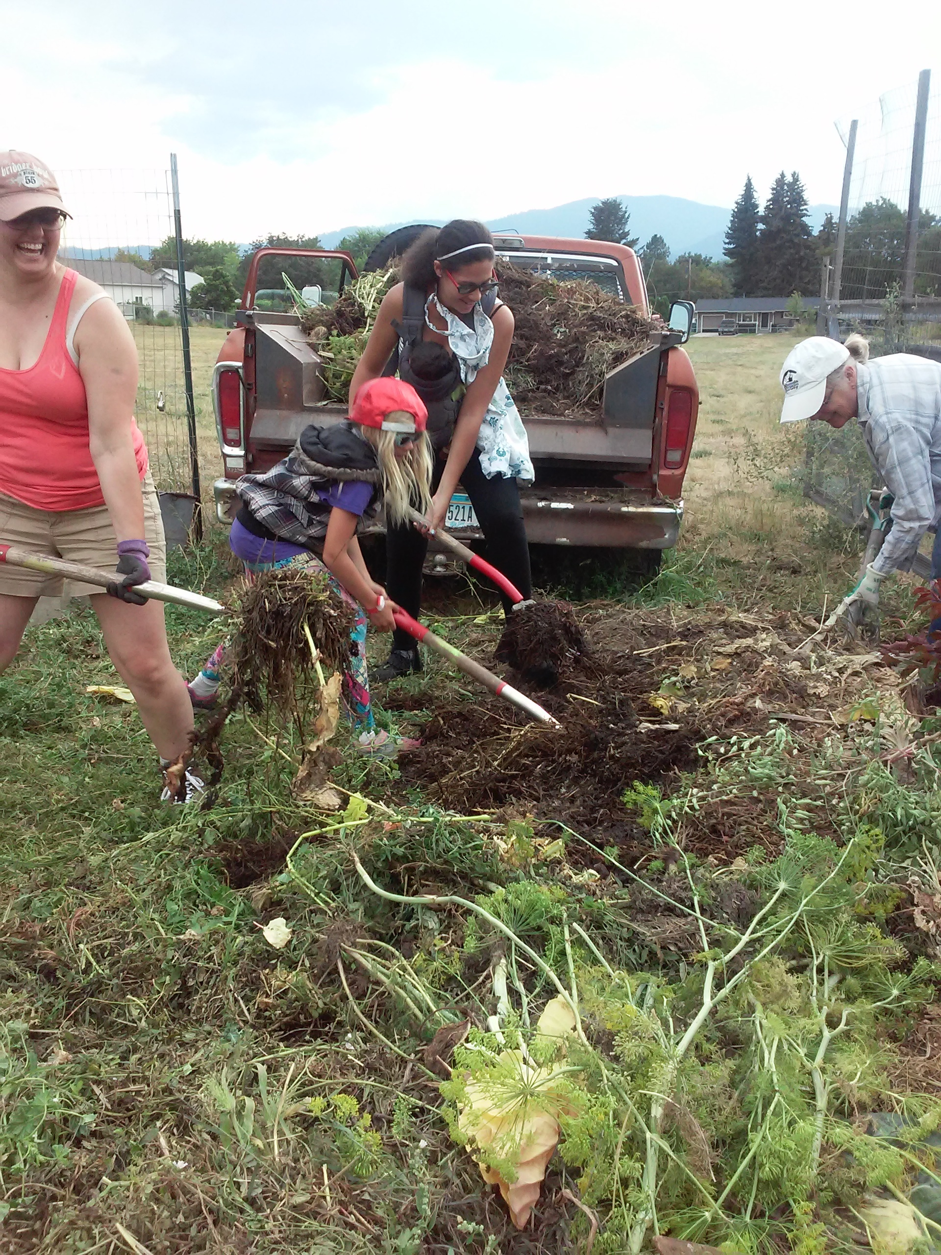 Meadow Hill leadership committee members and gardeners pitch in together to move the giant weed pile to another community garden with more space where it will eventually turn into compost.