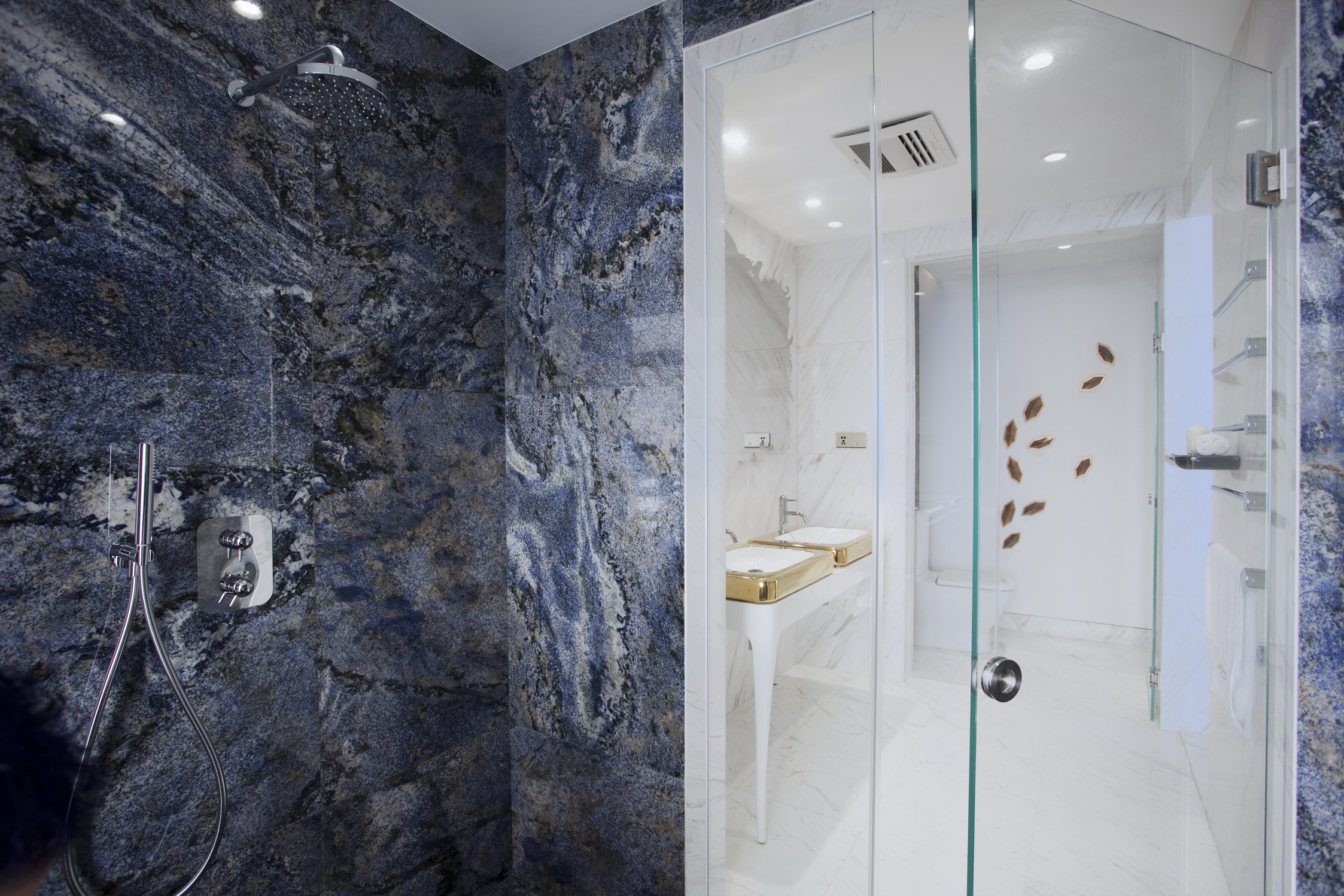 BATHROOM Blue marble stone walls and floor line the bath area. The bathtub is by Hayon for Bisazza