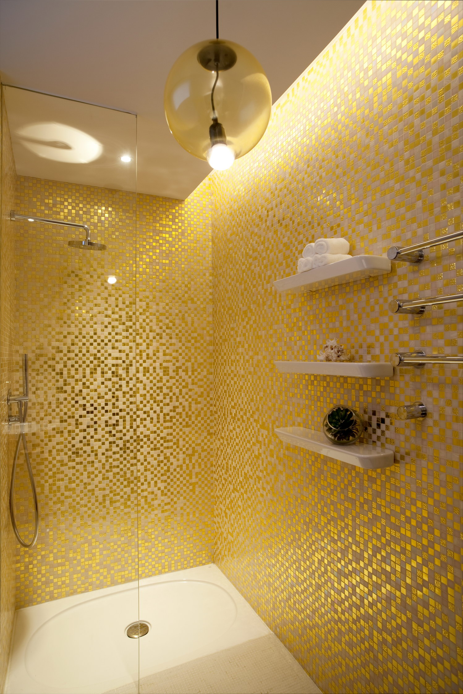 BATHROOM SHOWER Sparkling gold Bisazza mosaic tiles line the walls of the guest bathroom. The lighting fixture is by Bocci and bathroom accessories by Alessi Collection for Laufen.