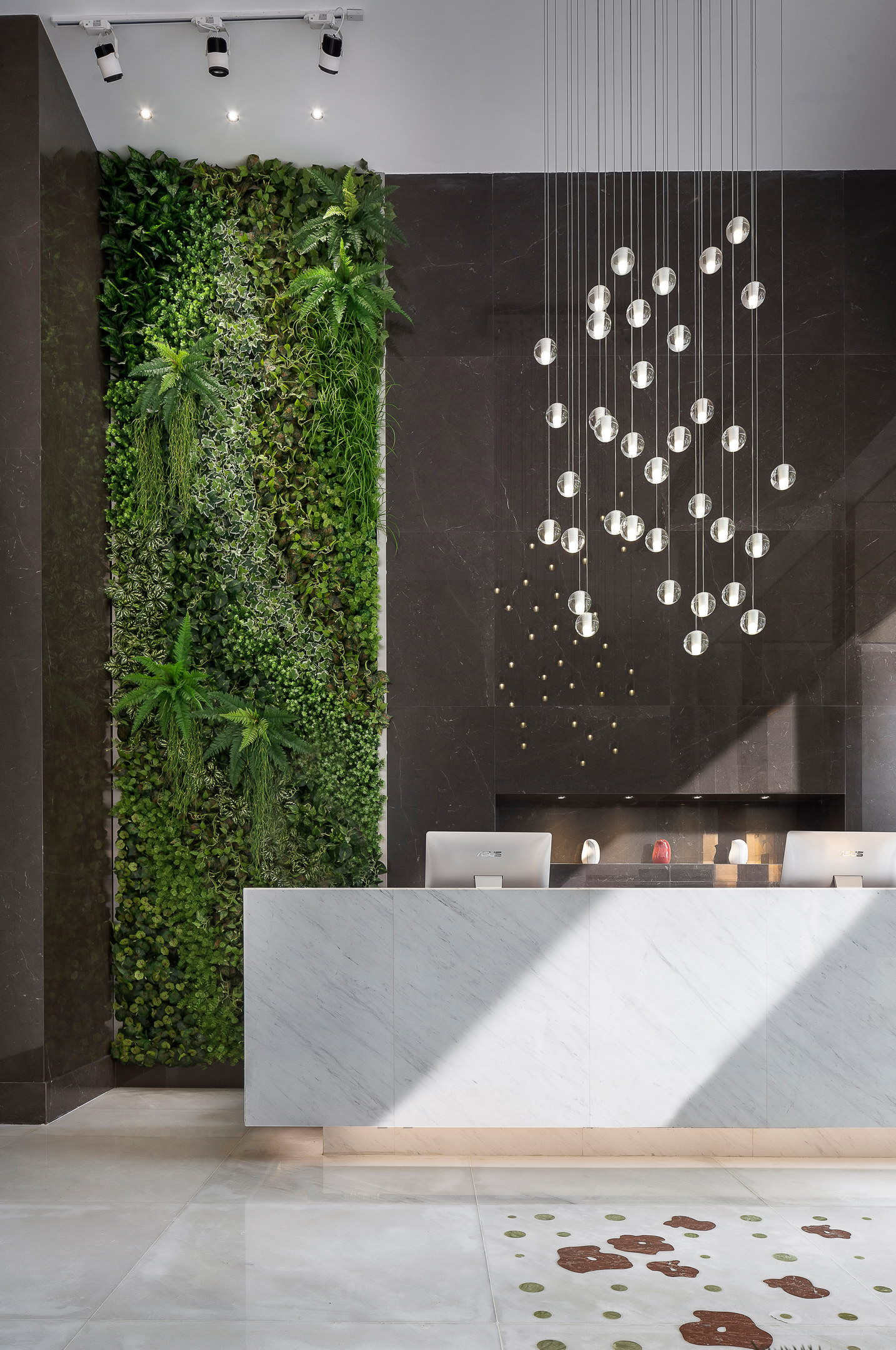 A green wall is set in a dialogue with the marble flowers on the floor