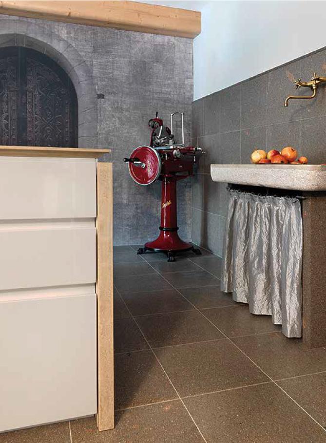 - Accanto: richiamo al passato il lavandino a parete, così come l'elegante affettatrice Berkel, sinonimo di una contemporaneità che ha alle spalle cento anni di storia professionale.In basso: primo piano delle sedie Eames Plastic Side Chair DSR di Charles & Ray Eames per Vitra, conosciute anche come