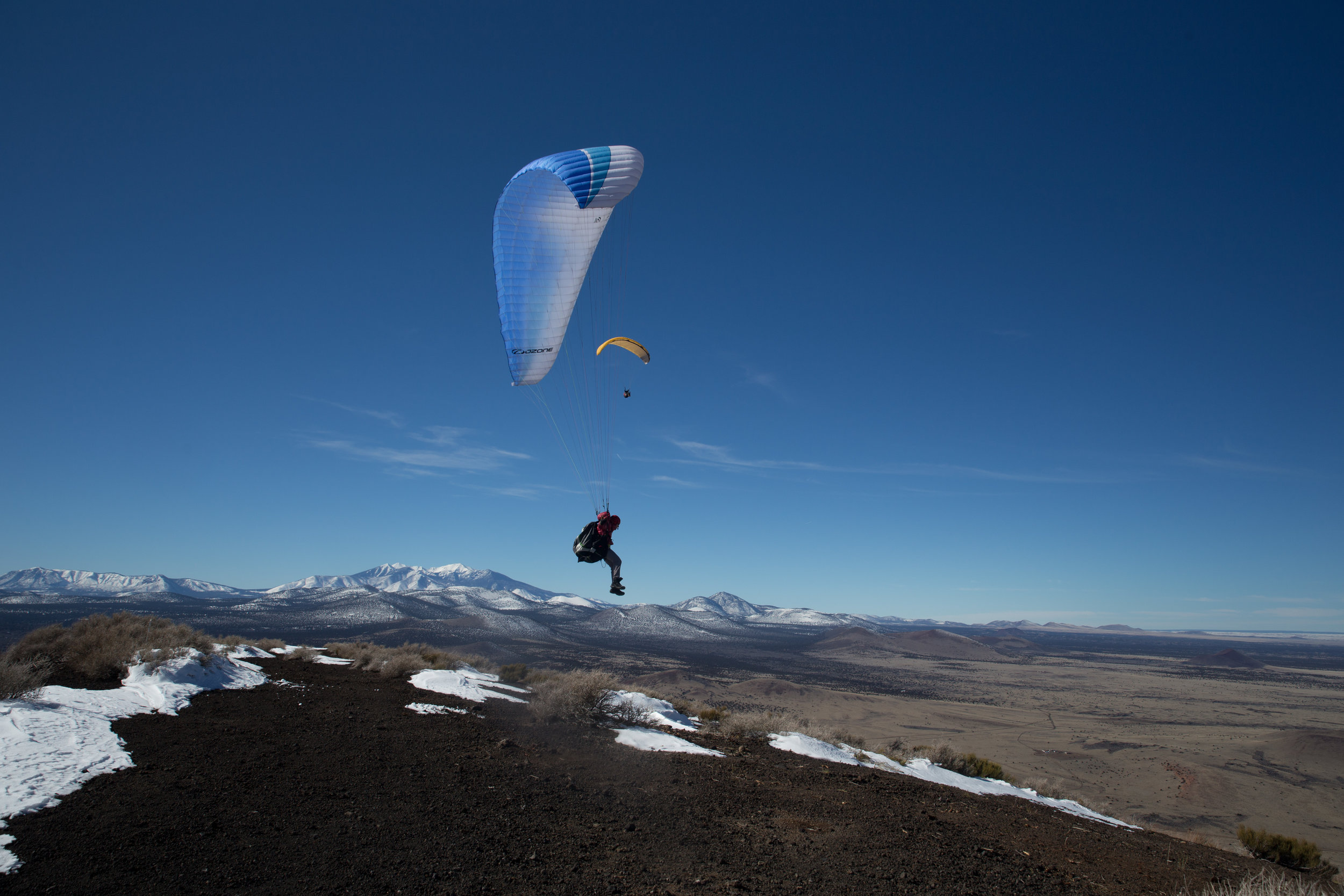 Paragliders find favorable winds atop Merriam Crater. The snow covered peaks sit quietly to the south west.
