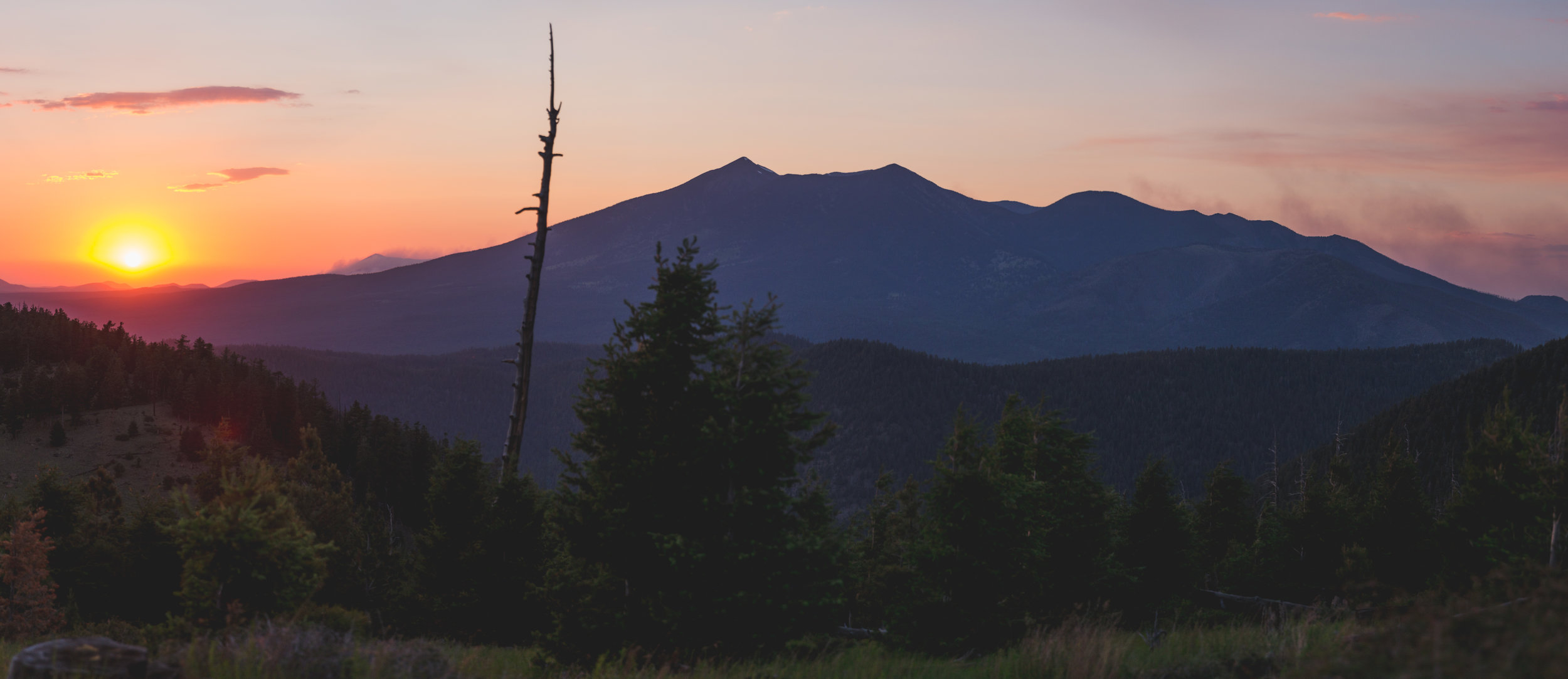 Smoke from wildfires brings a red-orange haze over the peaks, as viewed from atop Mount Elden