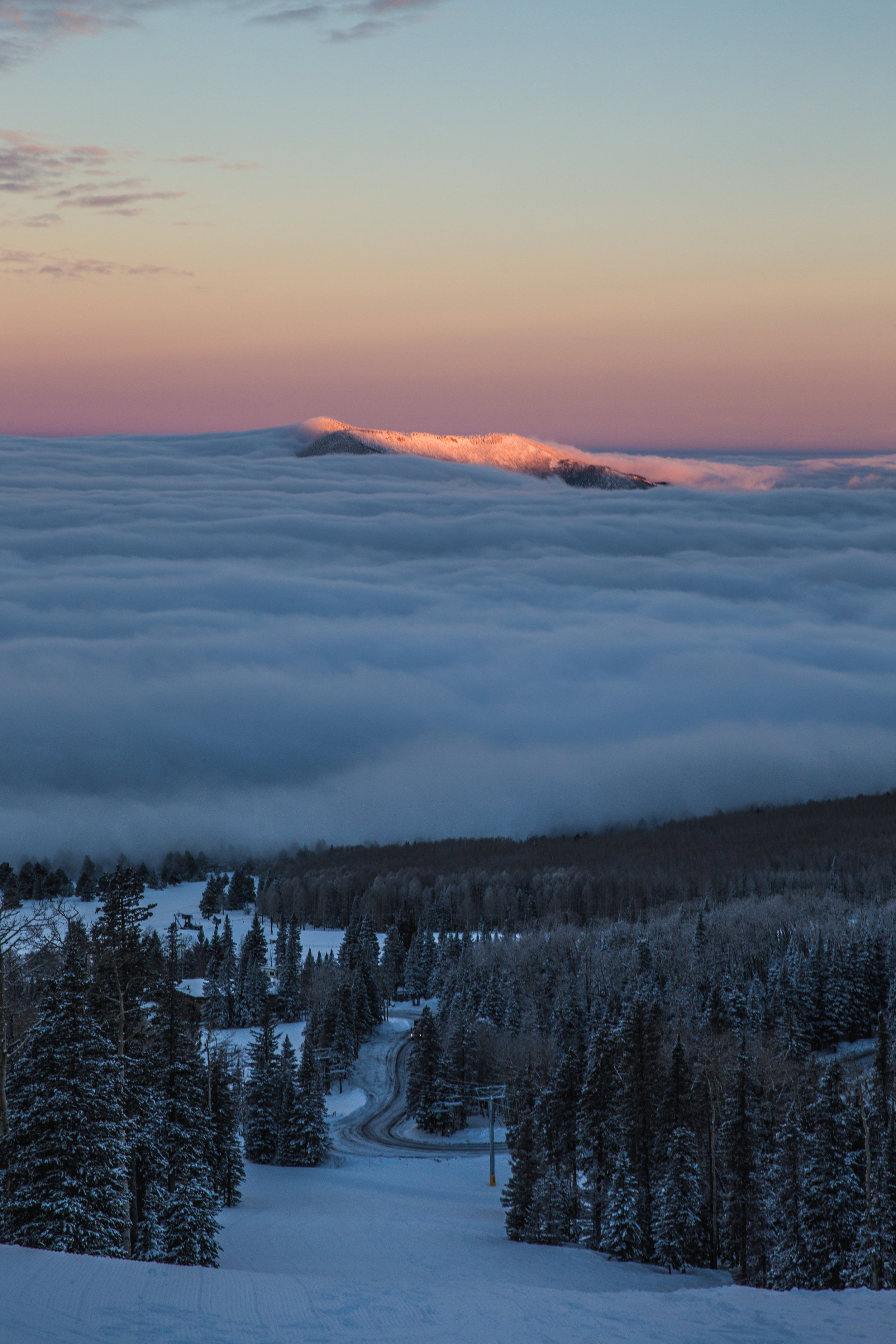 First Light hits Kendrick Peak above a layer of clouds. This picture was taken from Snowbowl. The presence of a ski resort on the mountain is controversial.