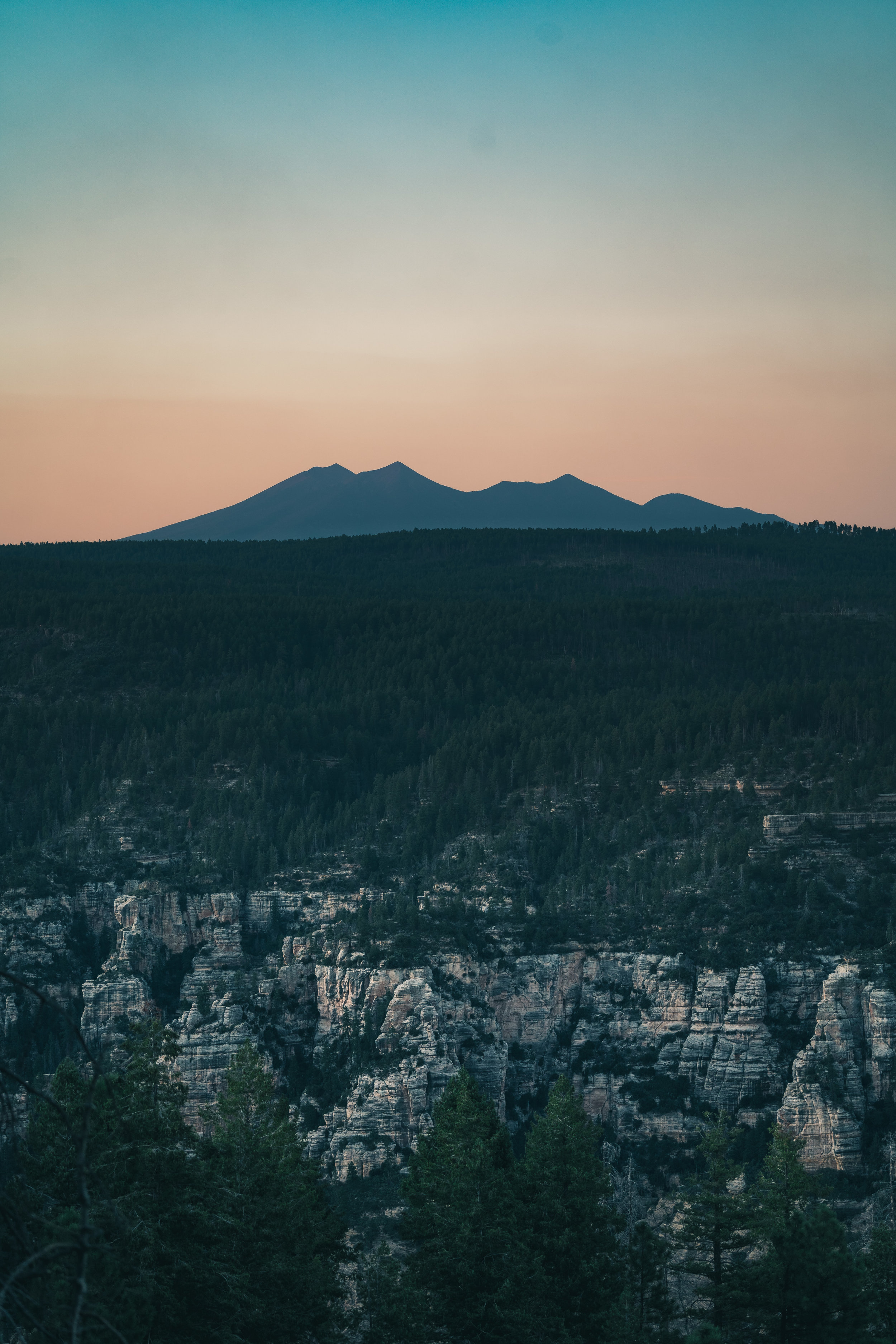 The West Fork of Oak Creek Canyon tears into the Colorado Plateau in the foreground, while San Francisco Mountain is silhouetted against the orange and teal twilight.