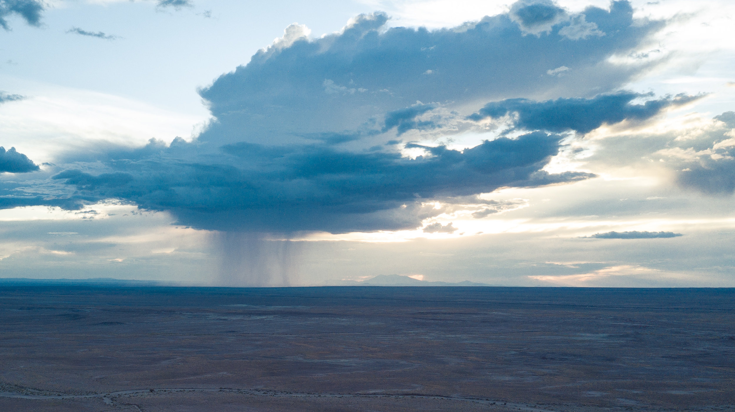 The peaks are barely visible along the horizon behind a large cumulonimbus cloud dumping moisture on the parched earth near Joseph City, AZ